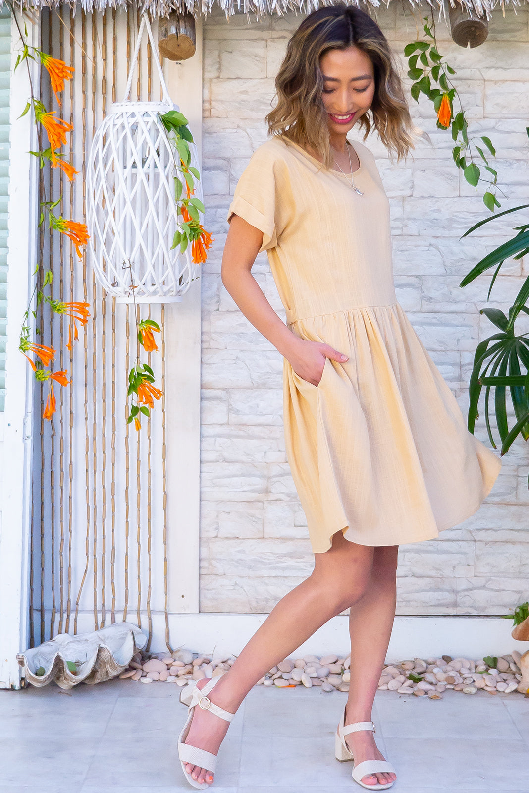 Blue Moon Corn Gold Dress features cuffed sleeves, drop waist, buttons and tabs at waist, side pockets and 30% Linen/ 70% Viscose in latte beige colour.