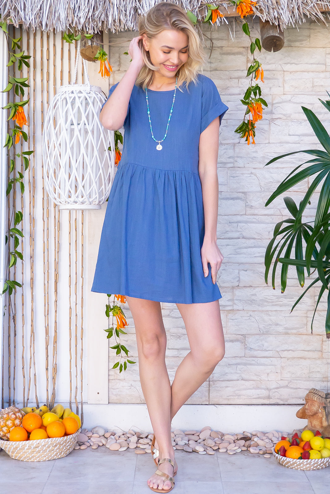 The Blue Moon Horizon Blue Dress is a loose fit, easy to wear frock featuring cuffed sleeves, drop waist, buttons and tabs at waist, side pockets and 30% Linen/ 70% Viscose in denim blue colour.