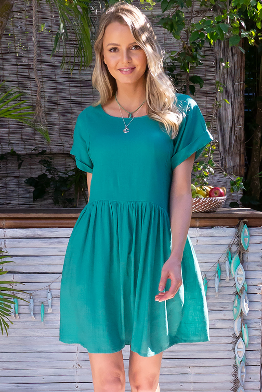 The Blue Moon Laguna Teal Dress is a loose fit, easy to wear frock featuring cuffed sleeves, drop waist, buttons and tabs at waist, side pockets and 30% Linen/ 70% Viscose in teal green colour.