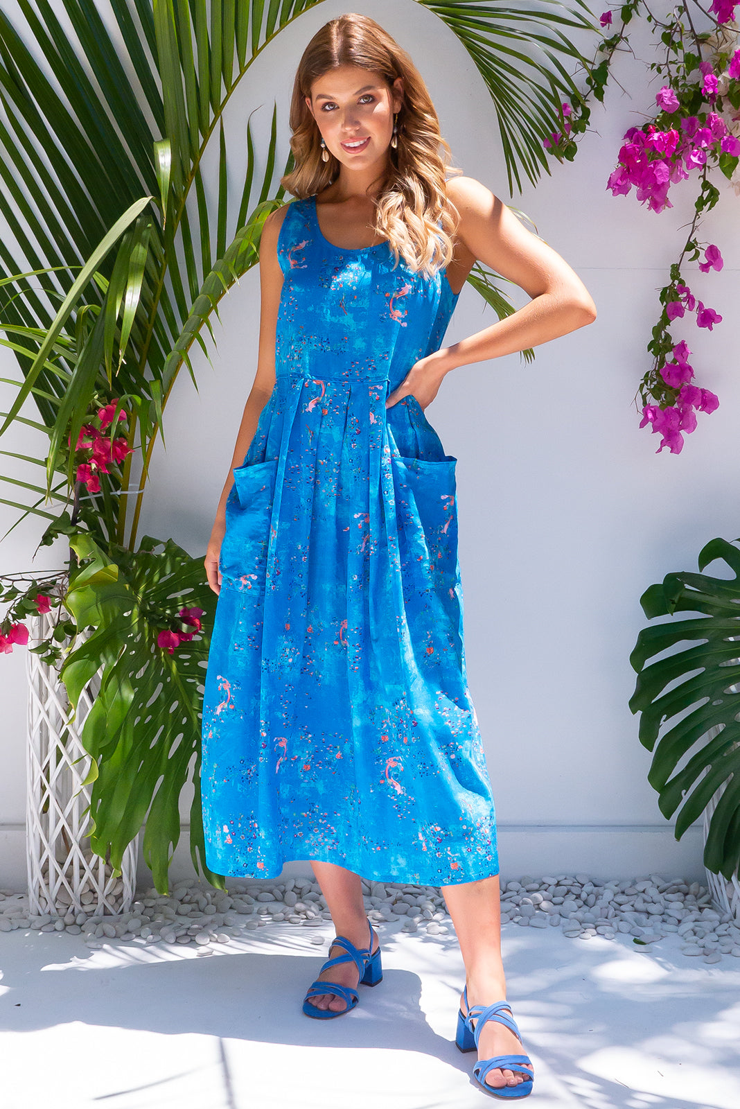 Bondi Beach Pacific Blue Dress, bohemian summers style, 100% cotton, slightly sheer, deep front pockets, adjustable waist with three coconut buttons on each side at the back allowing garment to be cinched, print placement will be different on all dresses, bright blue mottled colour with small navy, orange and white abstract print.