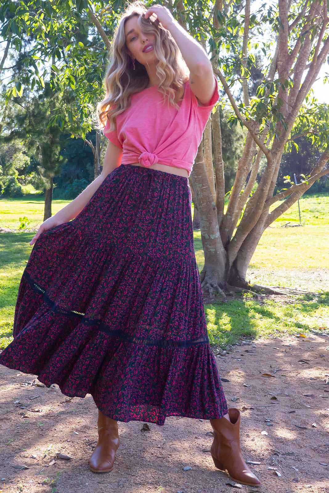 Bonnie Cerise Scattered Maxi Skirt is a tiered skirt and features an elasticated waist, side pockets and cotton insertion lace and it comes in a deep navy and cerise pink floral bohemian print of woven 100% rayon.