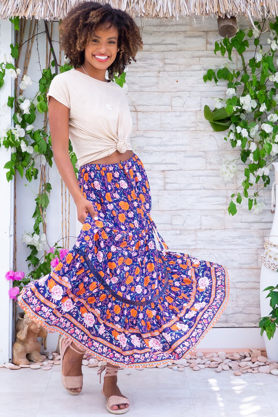 Bonnie Rambling Roses Navy Maxi Skirt features elasticated waist with adjustable drawstring tie, tiered, gathered skirt, a row of open work lace, side pockets, deep navy with a multi-tonal floral print, and order print features a bright orange in woven 100% rayon.