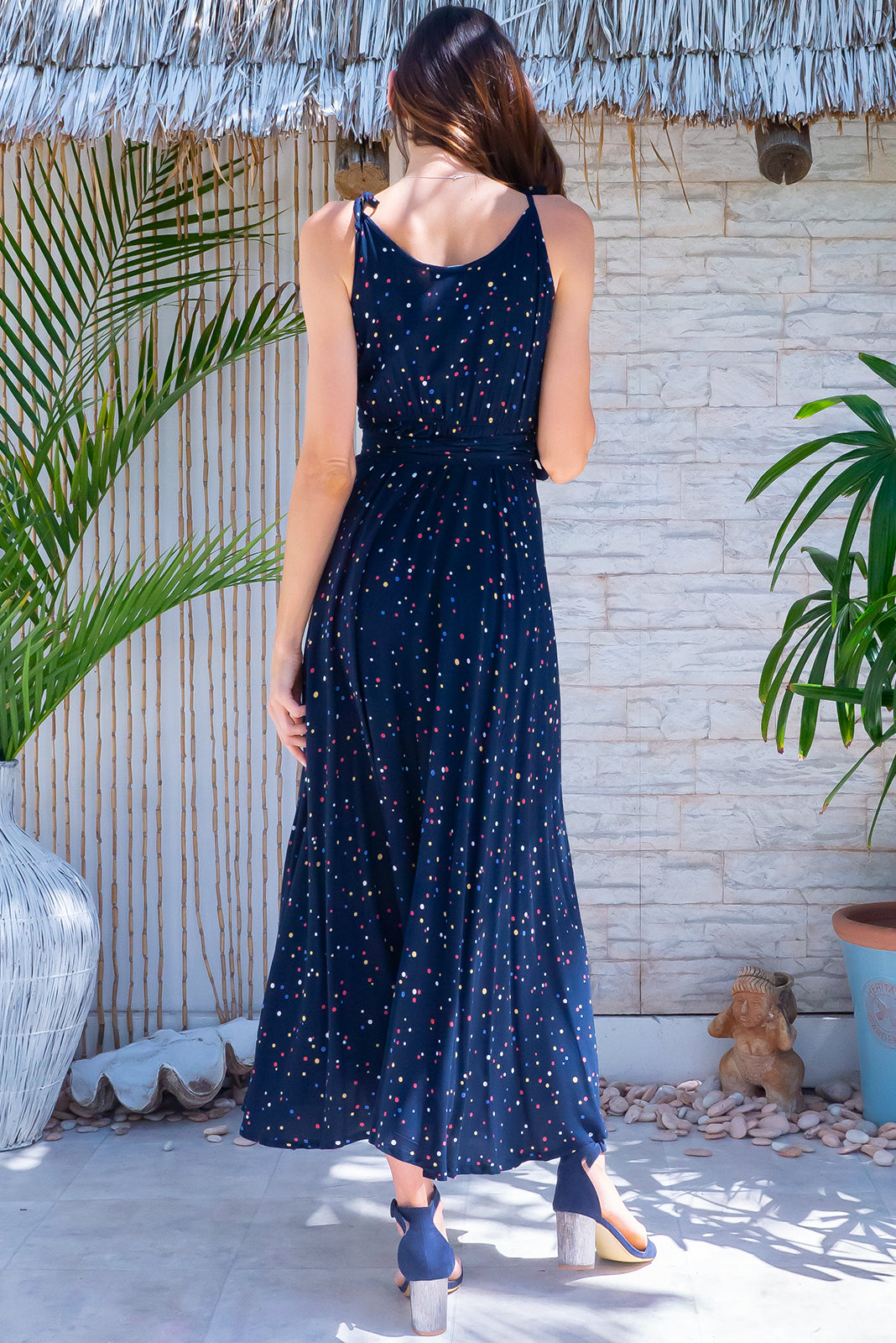 The Byron Ink Spot Maxi Wrap Dress is perfect for dinner dates and evening events, featuring functional wrap design, elastic back waist, adjustable shoulder ties and woven 100% rayon in navy base with small, multi-coloured polka dot design.