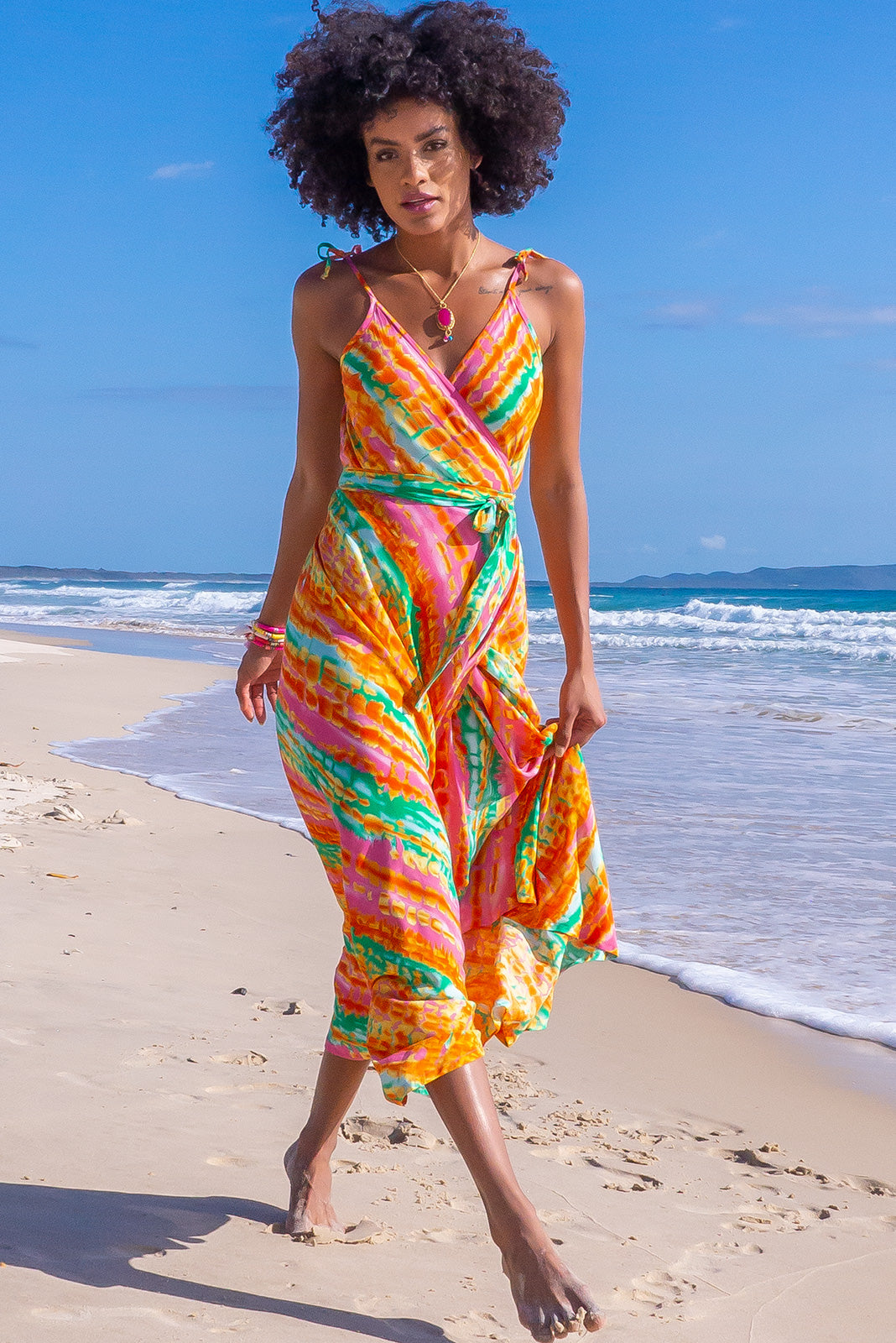 Hot island style, the Byron Sunset Tie Dye Maxi Wrap Dress features adjustable tie up shoulder ties, dress hem slightly longer at back, and 100% rayon in bright tie dye style print in white, orange, pink and green.