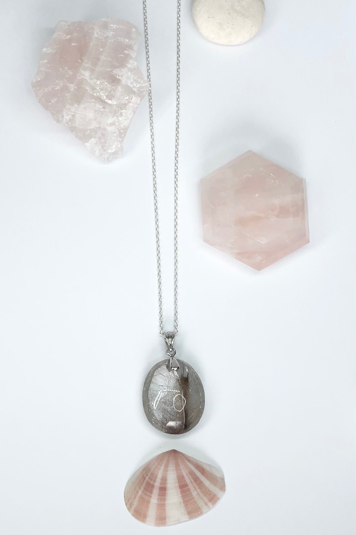 This is a very interesting natural crystal pendant polished to a high shine, this stone is cut in a symmetrical oval shape with the delicate silvery coloured Rutile needles showing on both sides.