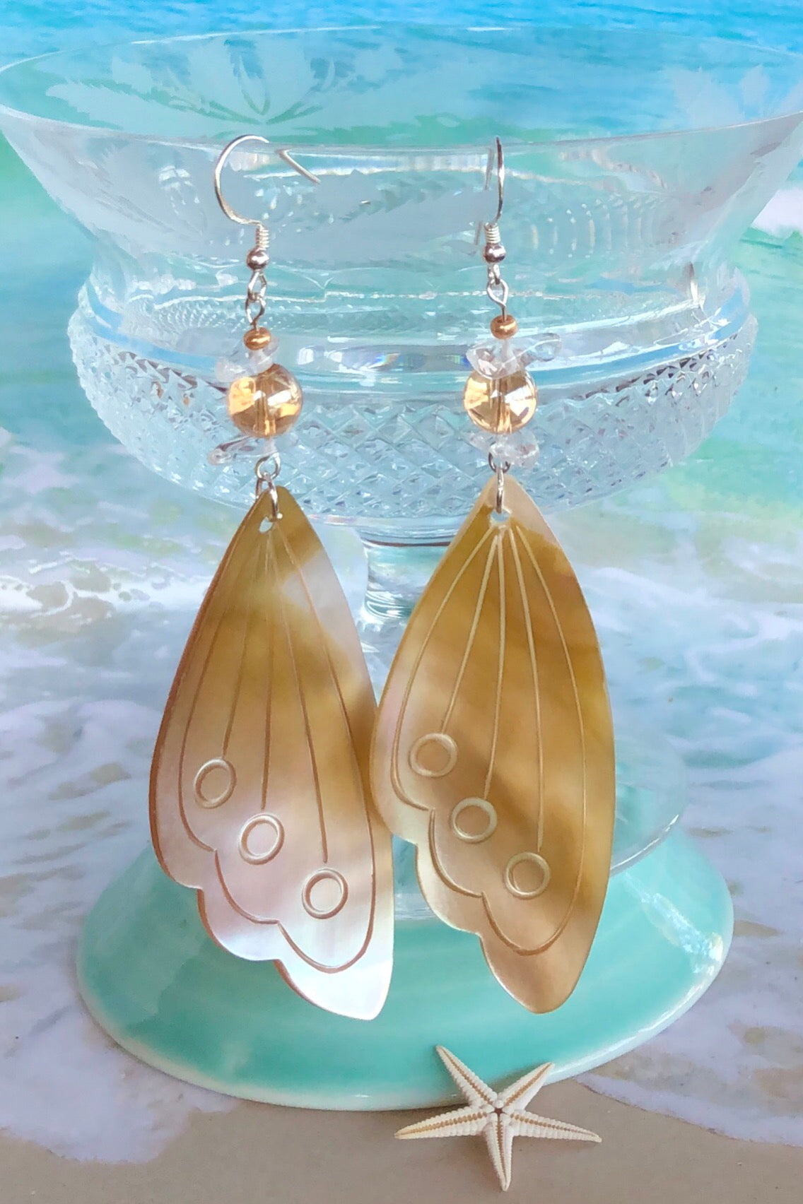 pale gold Mother of Pearl butterfly  wing has been hand cut and polished. At the top there is an iridescent crystal bead and a rock crystal bead.