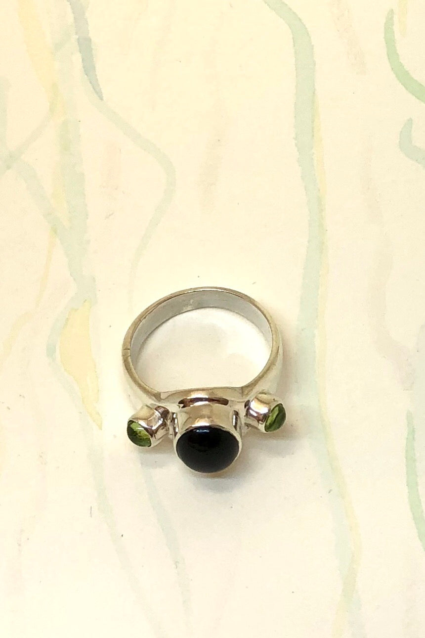 Echo Ring Onyx and Peridot is a powerful silver ring with black onyx cabachon set in 925 silver with Peridot side stones.