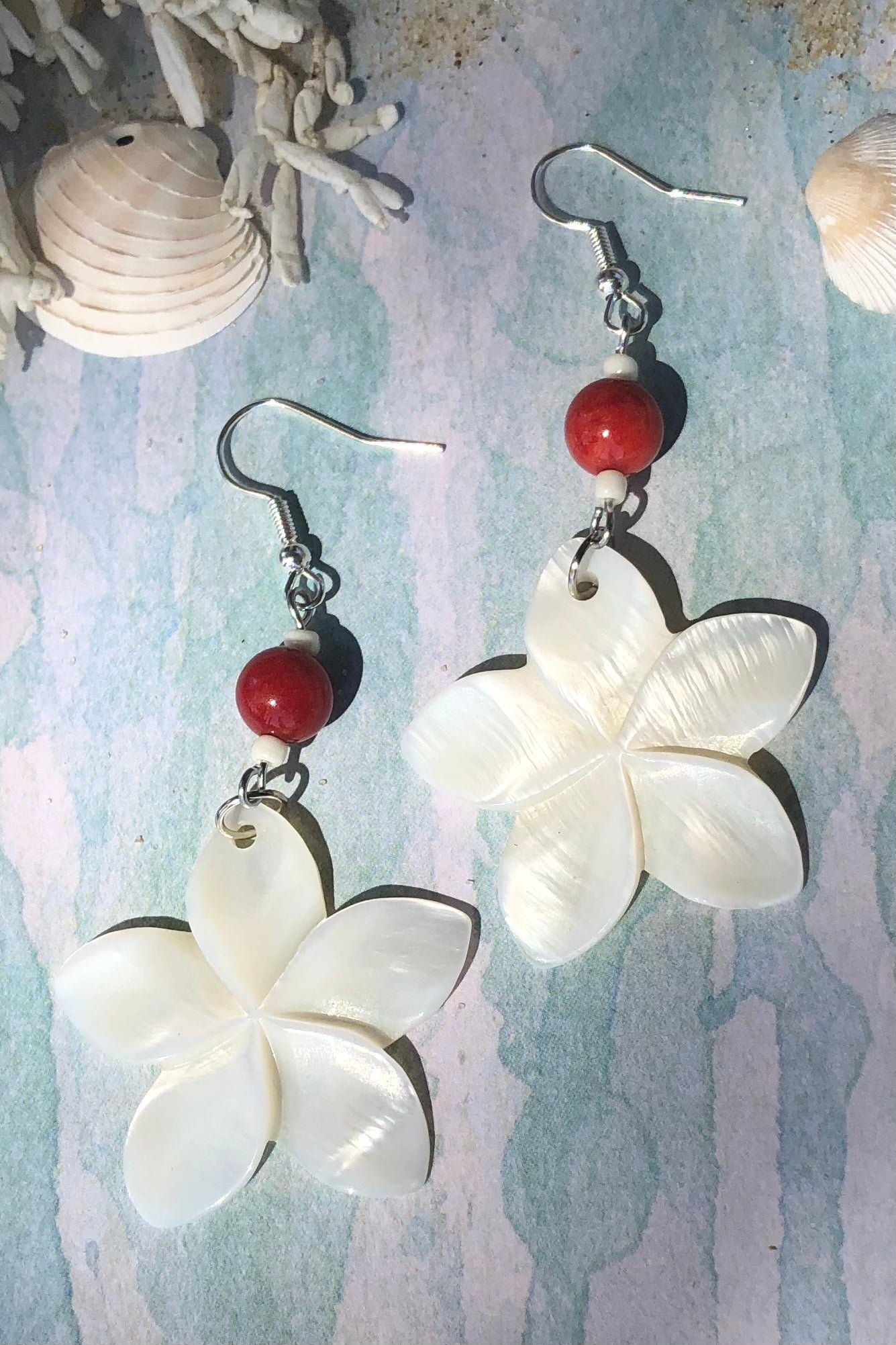 hese earrings with frangipani flowers hand carved from Mother of Pearl shell all carry the distinctive marks of the artist who created them