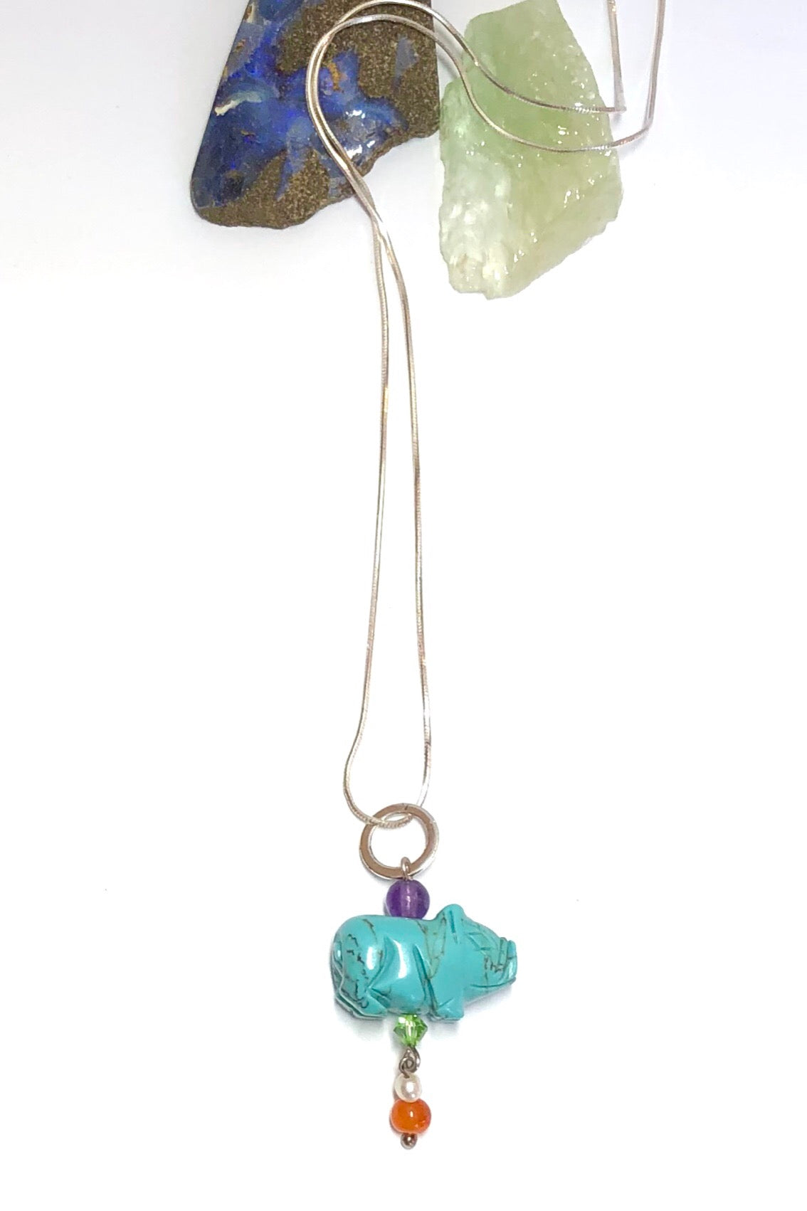 Pendant tiny Howlite Pig on Silver Chain features pig shape turquoise dyed Howlite gemstone with an amethyst top bead, Carnelian and pearl bead with a green crystal bead.