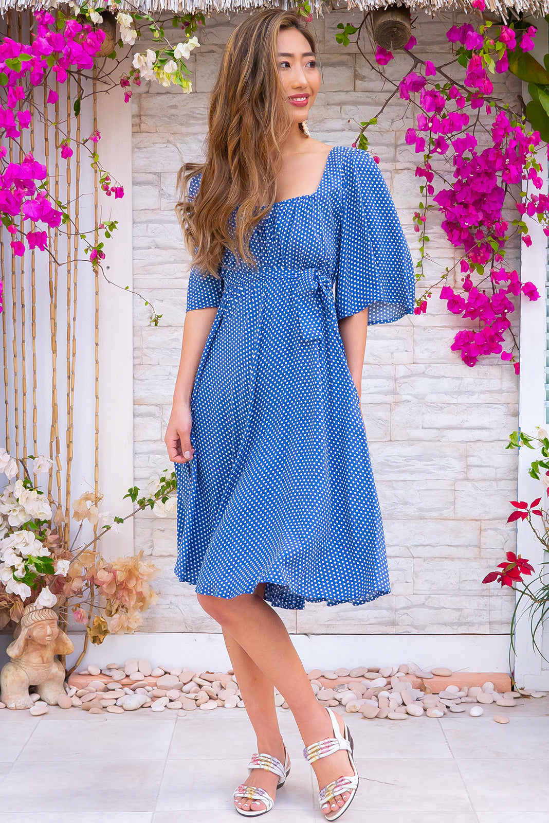 The Canterbury Retro Rita Dress is a vintage inspired polka dot blue summer frock made from 100% rayon, lightweight and breathable in a milkmaid cut neckline, includes side pockets and flutter sleeves.
