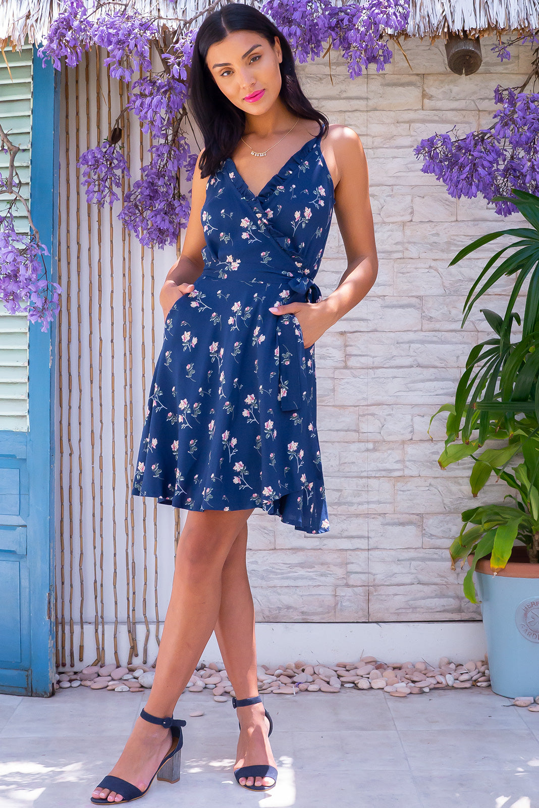 The Cappella Blue Roses Wrap Dress is a flirty and feminine frock featuring  frill detail over bust, adjustable straps, side pockets, functional wrap design with tie waist and 100% viscose in muted sapphire blue with romantic roses print.