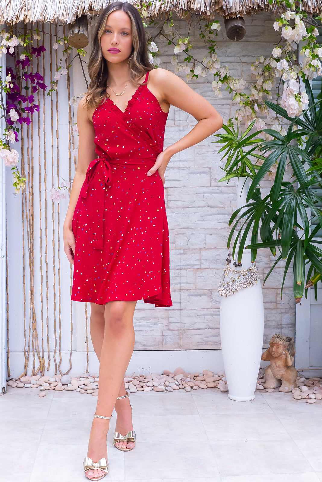 The Cappella Spotted in Red wrap Dress is functional wrap design with tie waist featuring frill detail over bust, adjustable straps, side pockets and 100% viscose in deep red base with multicoloured polkadot print.