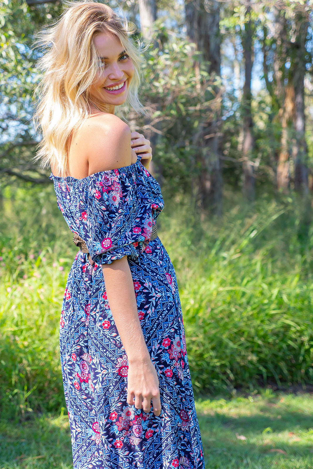 The Cecelia Elderberries Maxi Dress can be worn on or off the shoulder featuring gathered chest, elasticated under bust, decorative buttons on front of skirt, side pockets, frill hem and woven 100% rayon in navy base with bohemian print in blue, white and pink.
