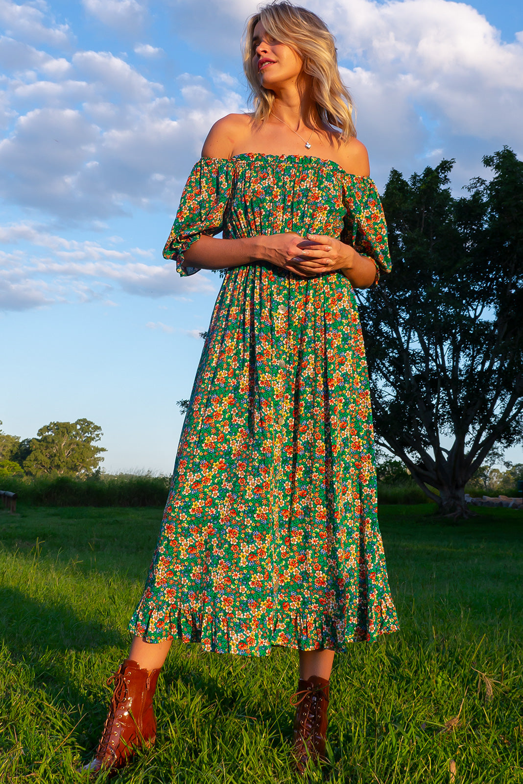 The Cecelia Green Leaves Maxi Dress can be worn on or off the shoulder of milkmaid style with puff sleeves and bust featuring ruched chest, elasticated under bust, decorative buttons on front of skirt, side pockets and the fabric is woven 100% rayon in emerald green base with retro multicoloured floral print.