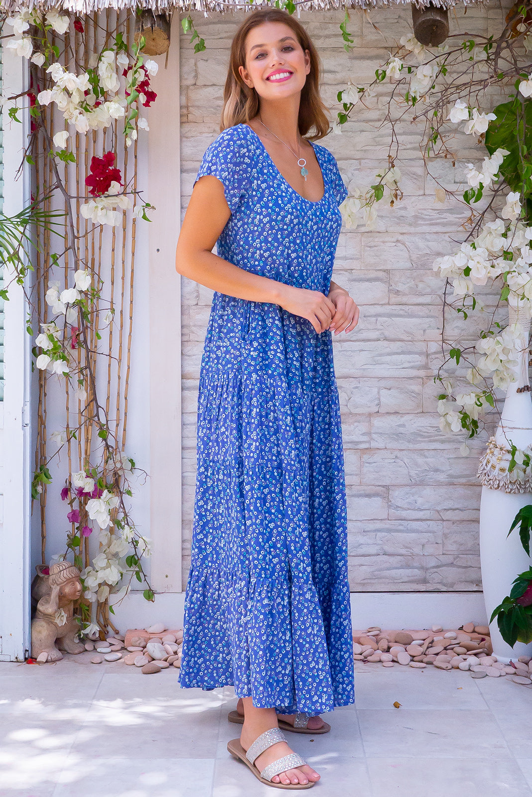 Celeste Skies Maxi Dress, bohemian summer style, 100% rayon, scoop neckline, capped sleeves, three tiered skirt, side pockets, bright blue base with small white and blue floral print.