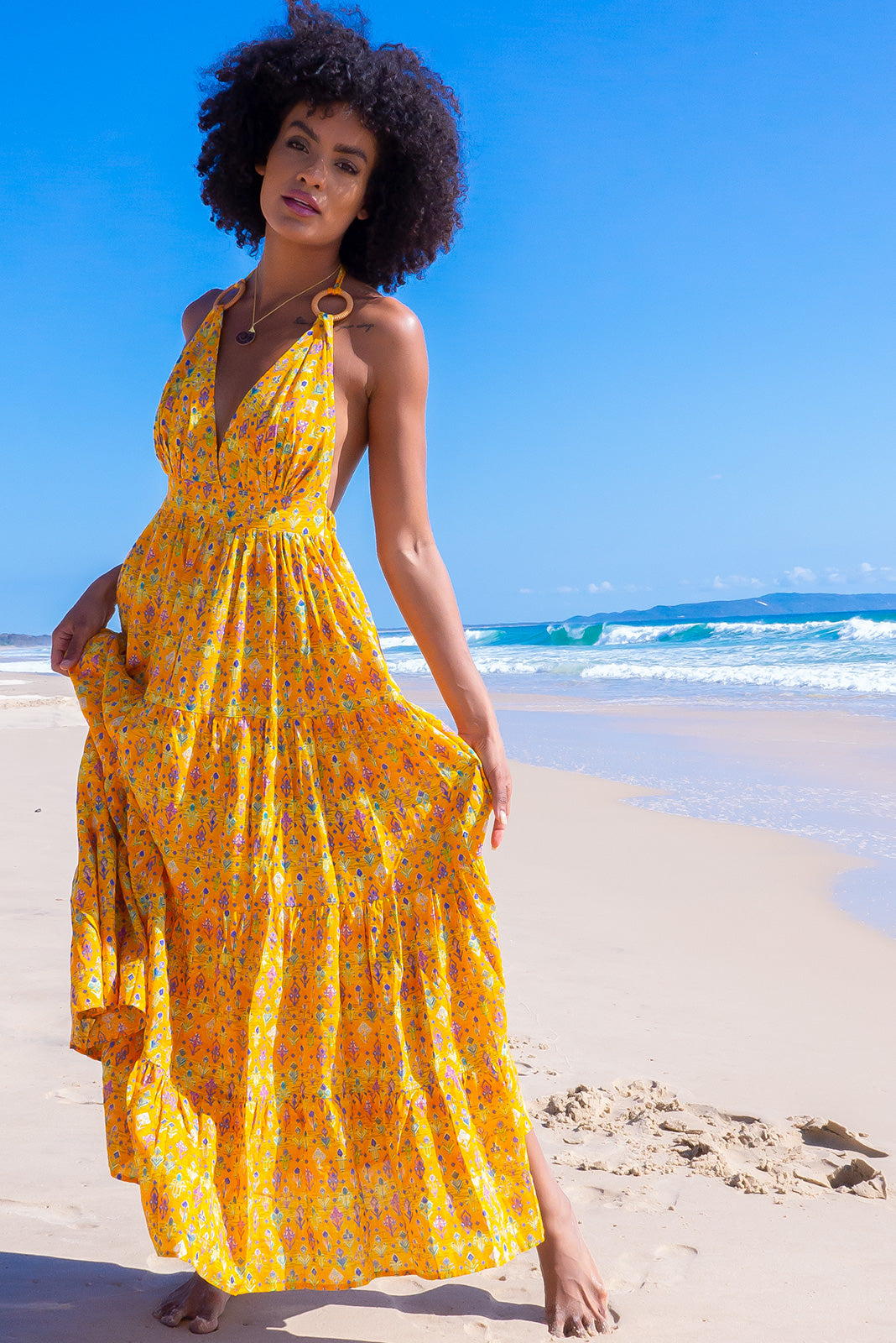 The Charlie Gold Aztec Maxi Dress is a summer must-have dress featuring elasticated back waistband, tiered skirt, deep side pockets and 100% cotton in golden yellow base with wash effect & multicoloured aztec print.