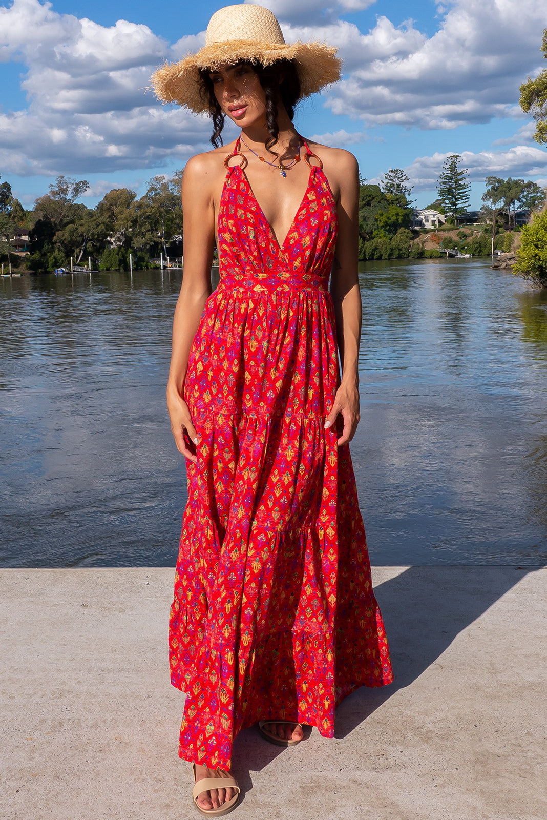 The Charlie Flame Aztec Maxi Dress is a backless dress featuring halter neck with tie up straps and ring feature elasticated back waistband, tiered skirt, side pockets and 100% cotton in vibrant red base with wash effect & multicoloured aztec print.