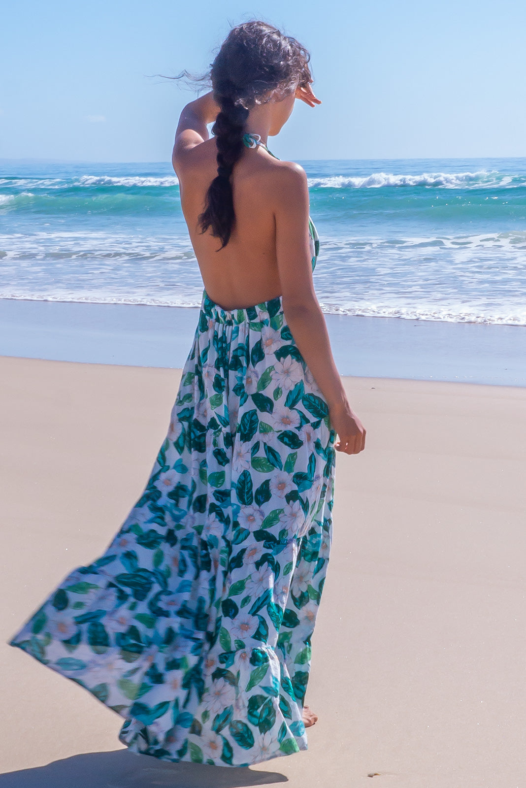 The Charlie White Knight Maxi Dress is a backless dress featuring halter neck with tie up straps and ring feature, elasticated back waistband, tiered skirt, deep side pockets and 100% cotton in white base with large white and green floral print.