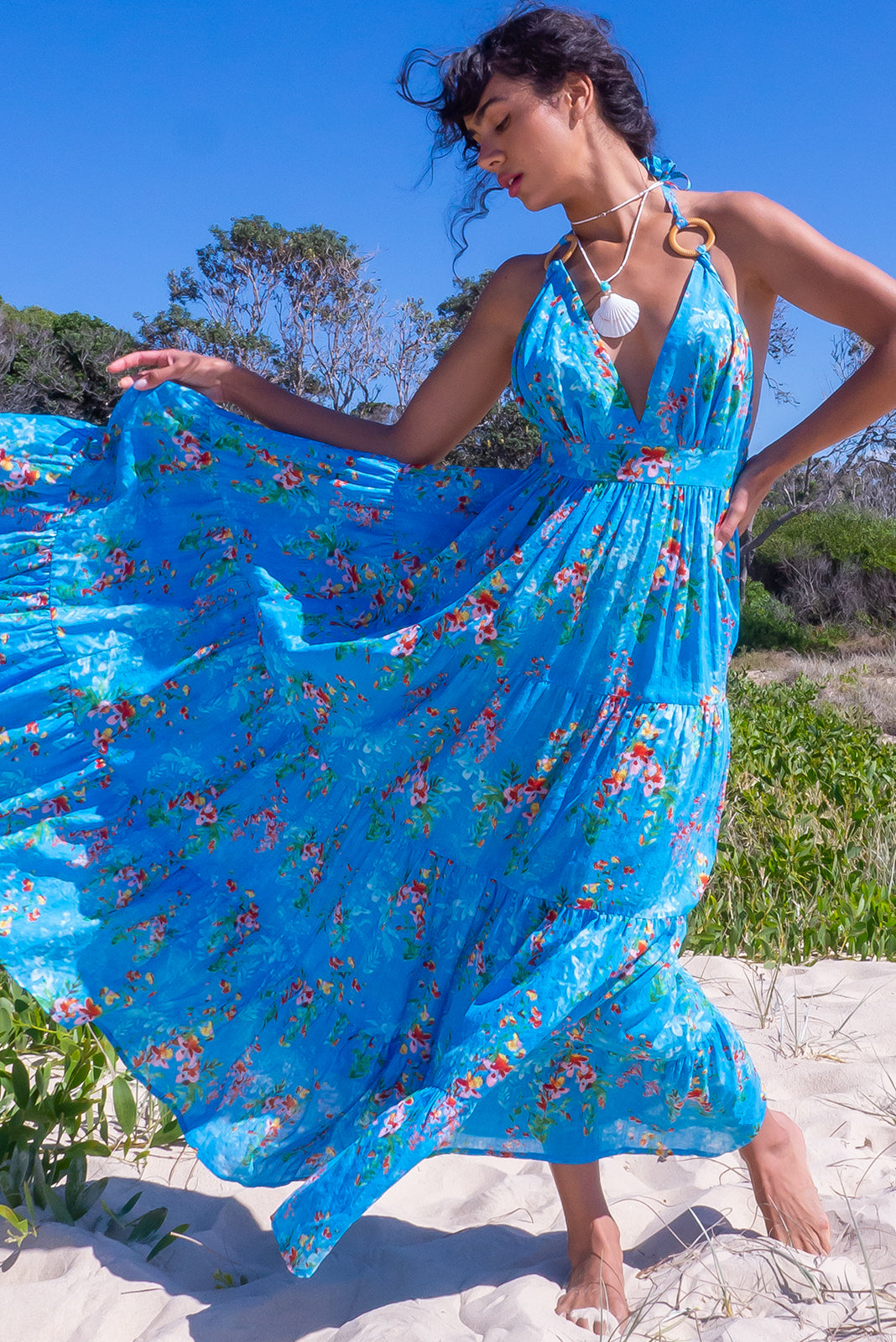 The Charlie Sea Glass Blue Maxi Dress is a perfect beach dress featuring halter neck with tie up straps and ring feature, elasticated back waistband, tiered skirt, side pockets and 100% cotton in vibrant blue base with wash effect & dappled print.