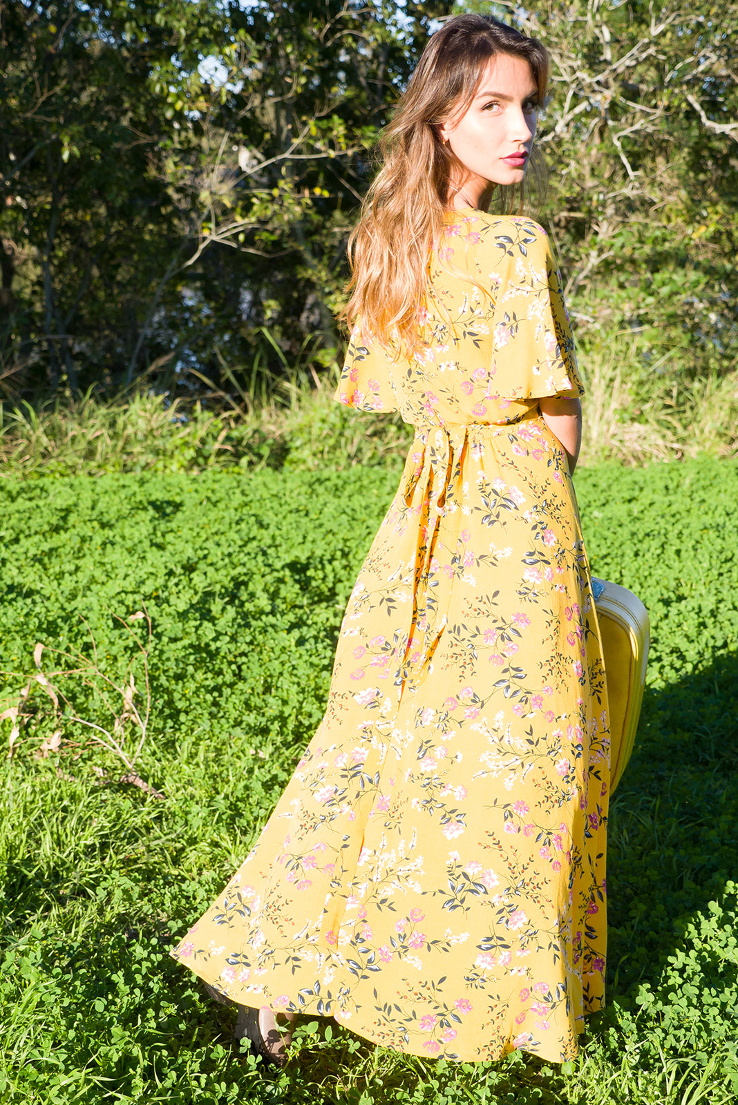 Cinnamon Garden Gold Maxi Wrap Dress, bohemian summer style, 100% rayon, wrap dress with tie at the waist, petal sleeve, soft bloused fit over the bust, scoop hem shorter at the front, crinkle crepe fabric with a soft drape, gold base with a medium red, white and forest green floral print.