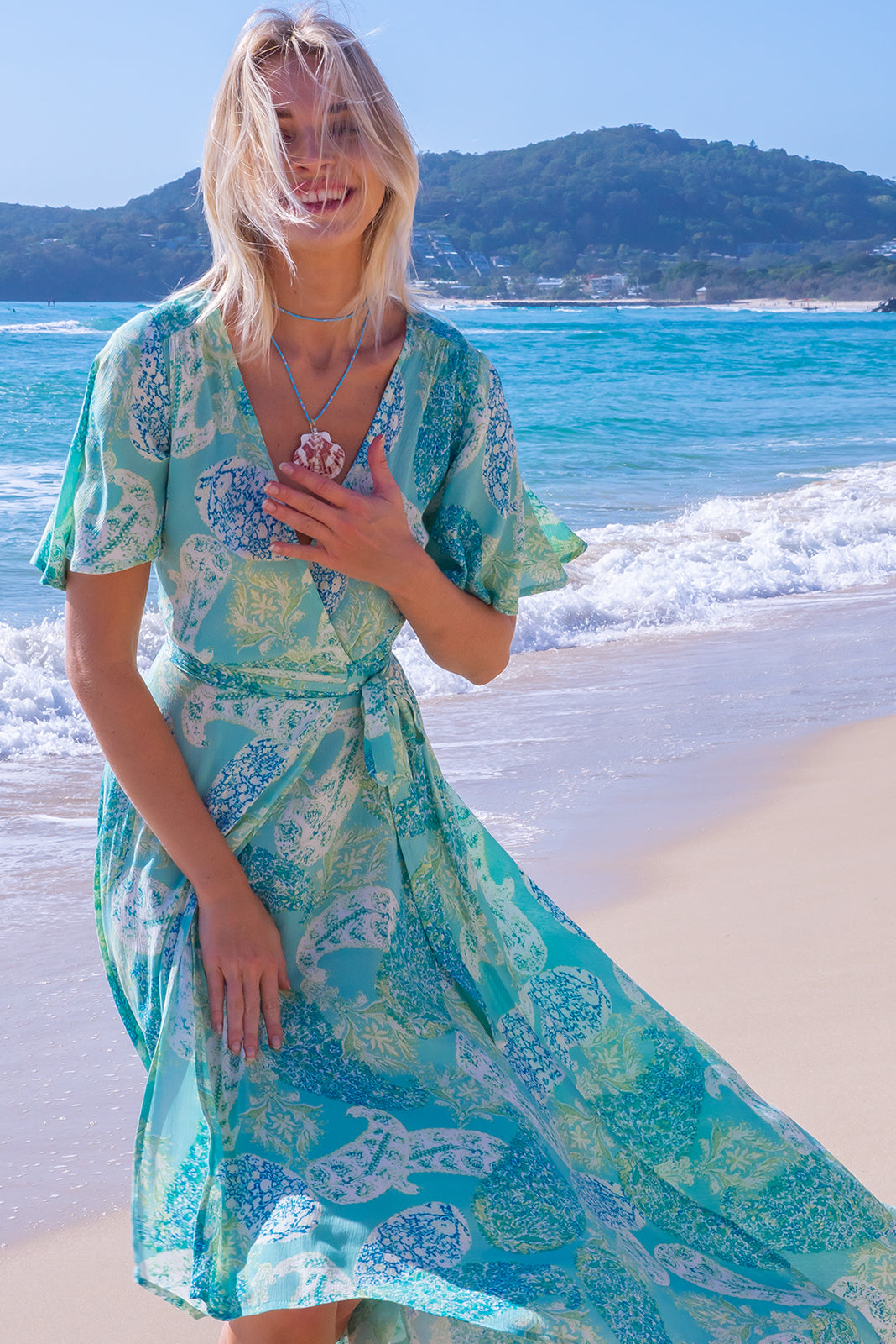 The Cinnamon Aquamarine Maxi Wrap Dress features flutter sleeves, adjustable wrap tie waist, elasticated back waist band, scooped hem, shorter at the front and crinkle 100% rayon in aqua/mint coloured large paisley design.