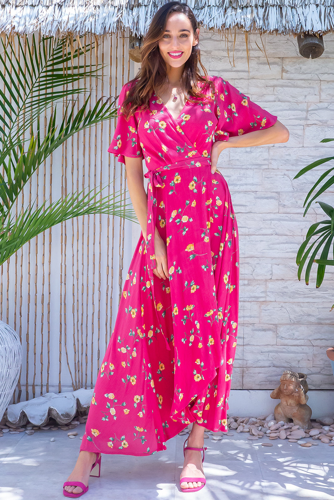 The Cinnamon Cerise Scatter Maxi Wrap Dress features adjustable wrap tie waist, elasticated back waist band, flutter sleeves, scoop hem shorter at the front and 100% crinkle texture rayon in cerise pink base with amber toned floral print.