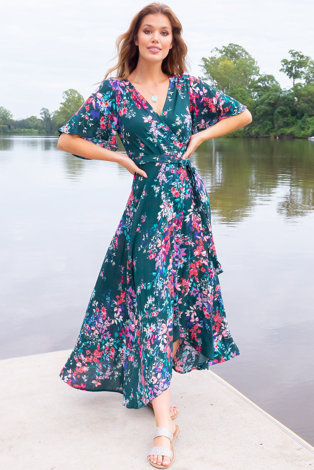 The Cinnamon Forest Green Maxi Wrap Dress is a nature-inspired frock featuring crinkle textured woven 100% rayon, flutter sleeves, V neckline adjustable wrap tie waist, elasticated back waist band, scooped hem, shorter at the front and deep forest green base with multi-coloured floral design.