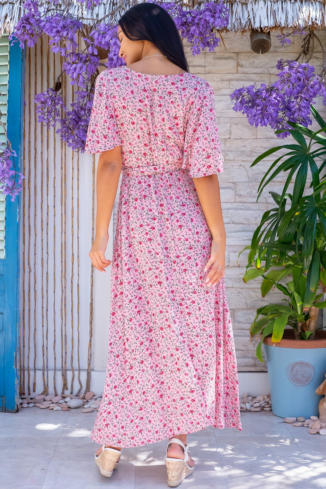 The Cinnamon Pink Blush Maxi Wrap Dress features adjustable wrap tie waist, scooped hem, shorter at the front and crinkle textured rayon in soft pink base with small floral print.