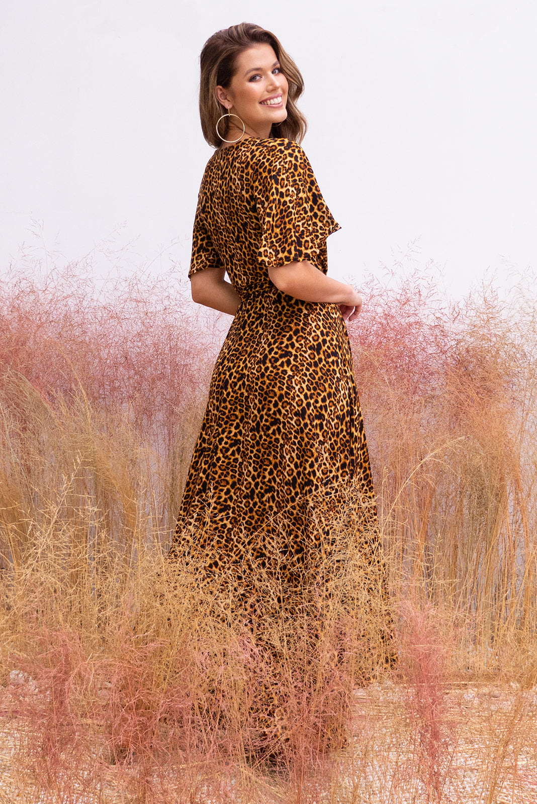 Cinnamon Wild Things Maxi Wrap Dress bohemian inspired safari vibe dress featuring petal sleeves, wrap around waist, waterfall hemline in a woven crinkle textured 100% rayon fabric bold strong leopard skin print.
