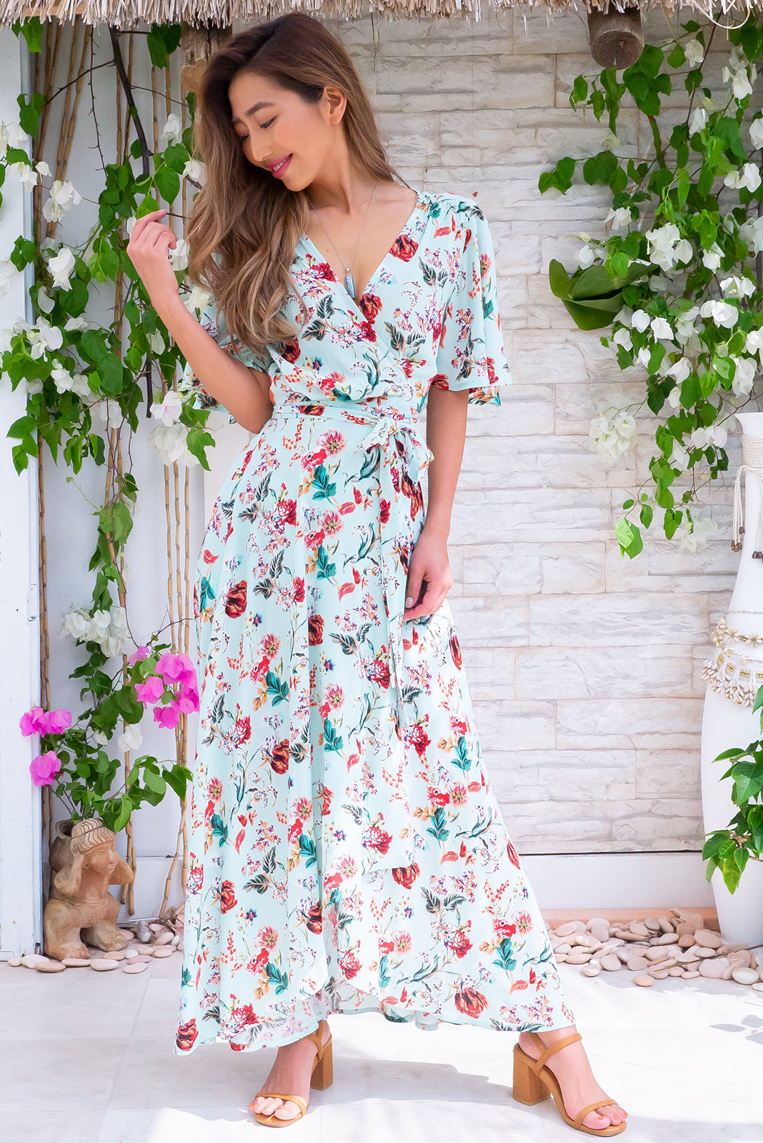 Cinnamon Giverny Mint Maxi Wrap Dress, airy wrap-style frock features, flutter petal sleeves, V neckline, adjustable wrap tie waist, elasticated back waist band, scooped hem, shorter at the front in bright mint base with red, orange, white floral design in crinkle textured woven 100% rayon.