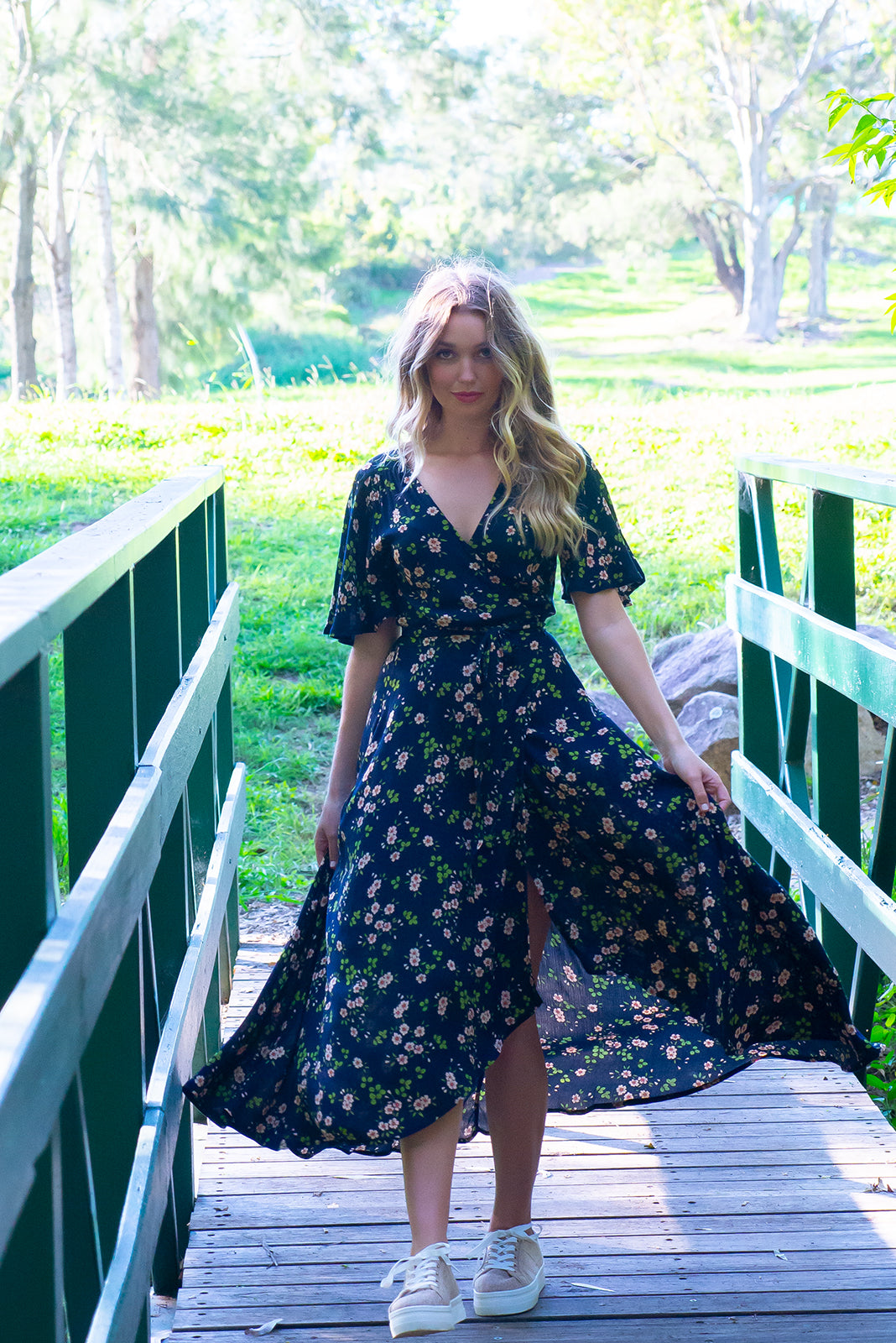 Cinnamon Navy Celeste Maxi Wrap Dress features a beautiful classic ditzy daisy floral bohemian print on a soft woven crinkle textured rayon a, it has a petal sleeve and a flattering adjustable wrap waist