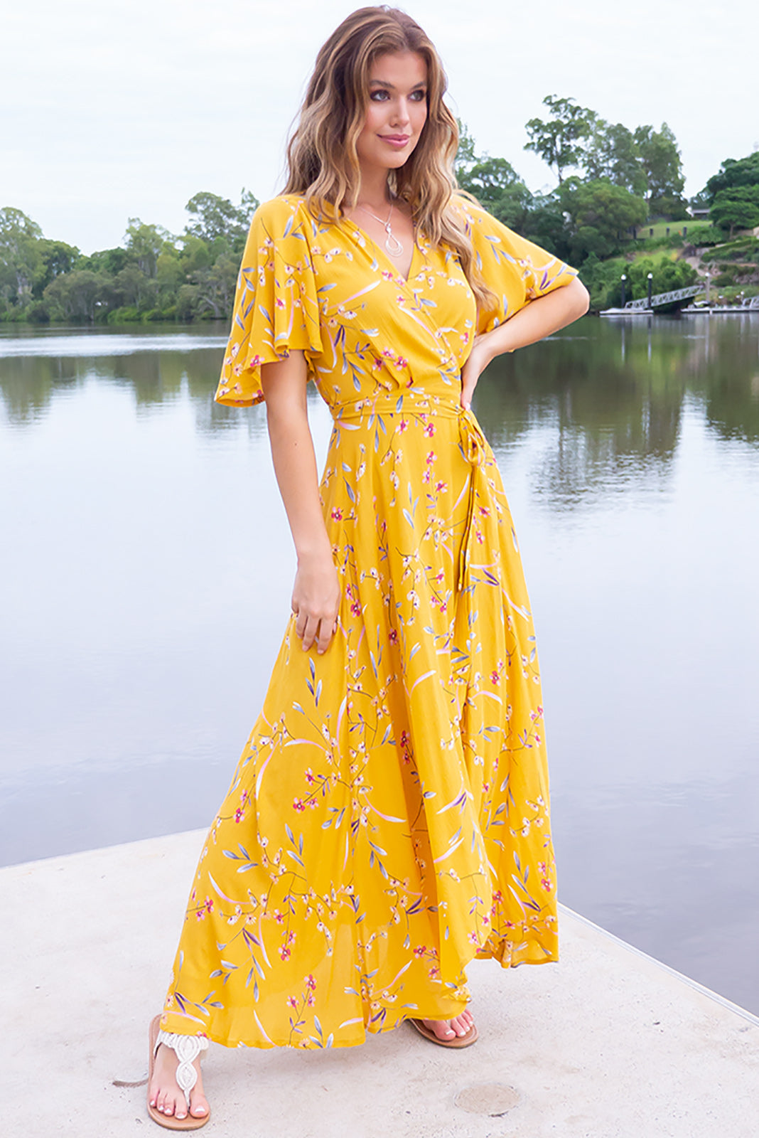 The Cinnamon Nectar Gold Maxi Wrap dress is sweet and summery featuring flutter sleeves, adjustable wrap tie waist, elasticated back waist band, scooped hem, shorter at the front, warm gold base with multi-coloured floral design featuring pastel pink, fuchsia and grey in crinkle textured woven 100% rayon.