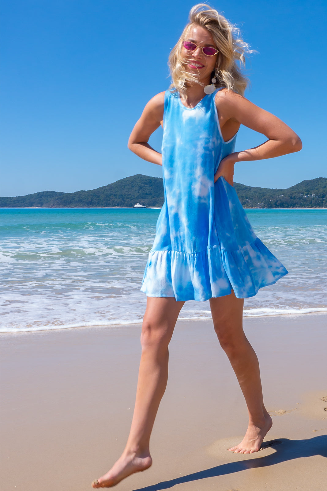 Perfect beach frock, the Cloudland Blue Skies Swing Dress features back neck tie, sleeveless, breezy skirt, side pockets and 100% rayon in blue and white tie dye.
