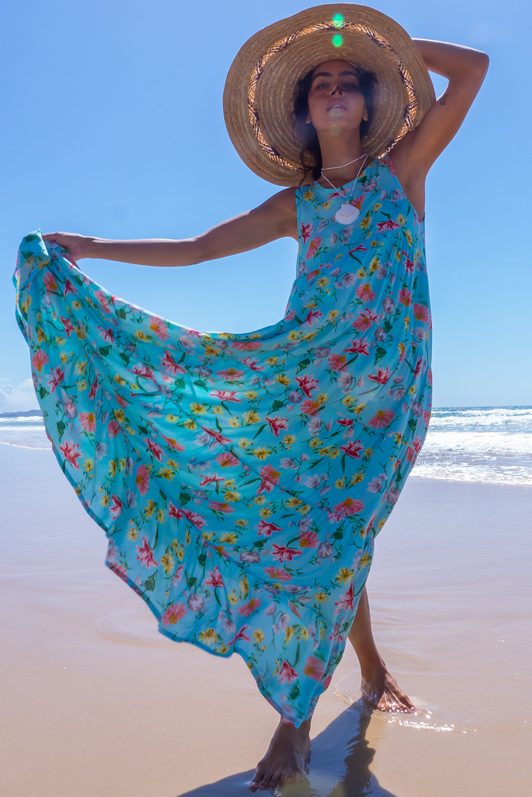 The Cloudland Dream Flowers Aqua Maxi Dress is a Sleeveless dress featuring back neck tie, tiered skirt, side pockets and 100% rayon in sky blue base with spring floral print.