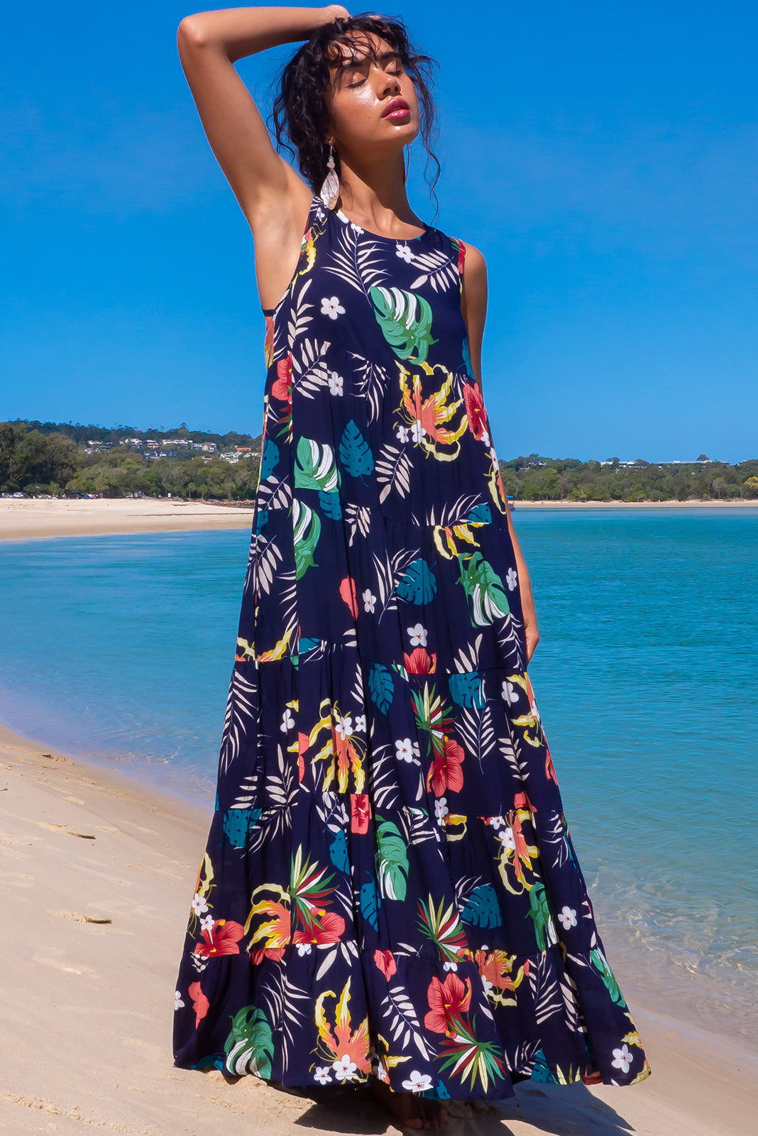 The Cloudland Navy Chic Maxi Dress features back neck tie, sleeveless, breezy, tiered skirt, side pockets and 100% rayon in ink base with tropical print.