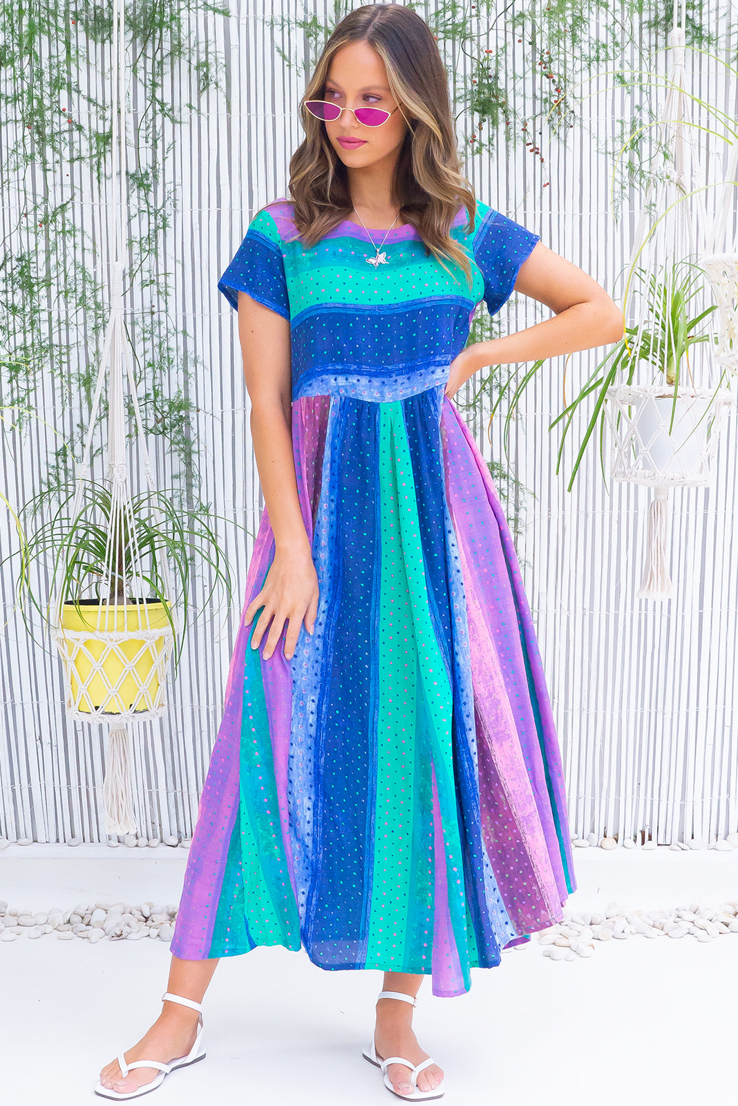 The Cocoloco Glacier Blues Midi Dress features fabric is slightly sheer when against the light, short sleeves, side pockets and 100% cotton in soft blue and purple toned tie dye style stripes.