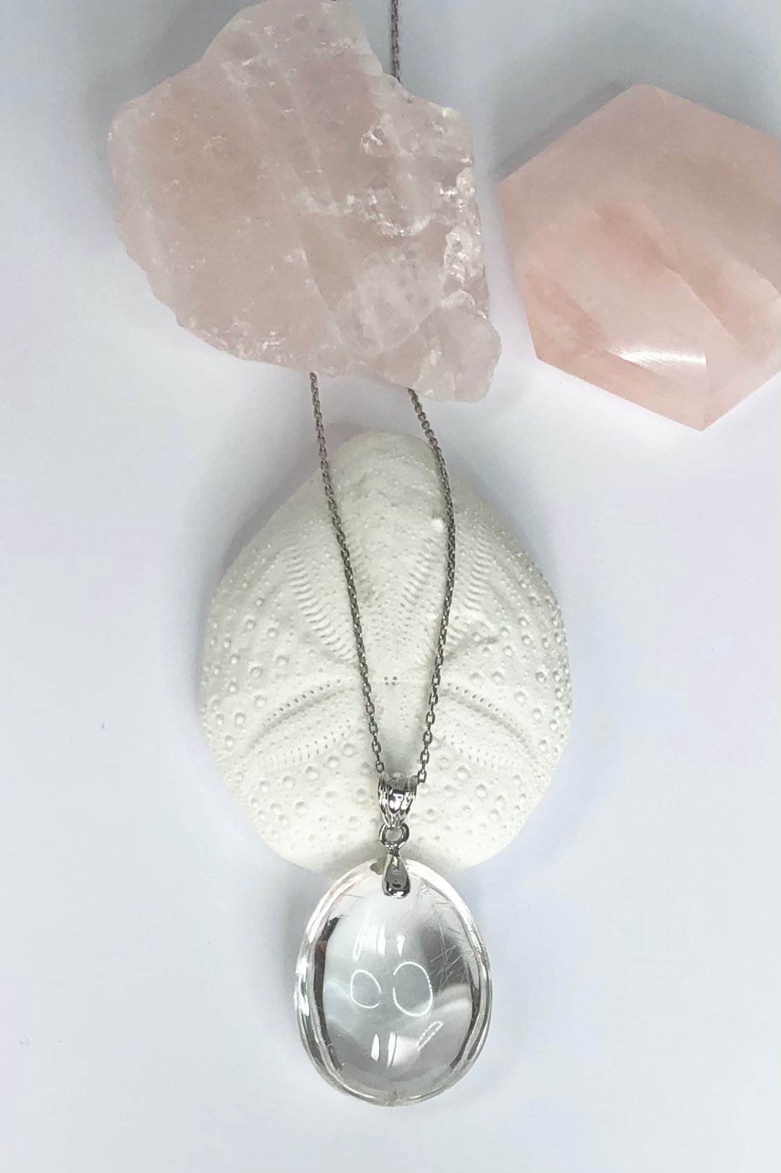 his pure and lovey natural crystal pendant is polished to a high shine, this stone is cut in a symmetrical oval shape with the delicate silvery coloured Rutile needles showing on one side.