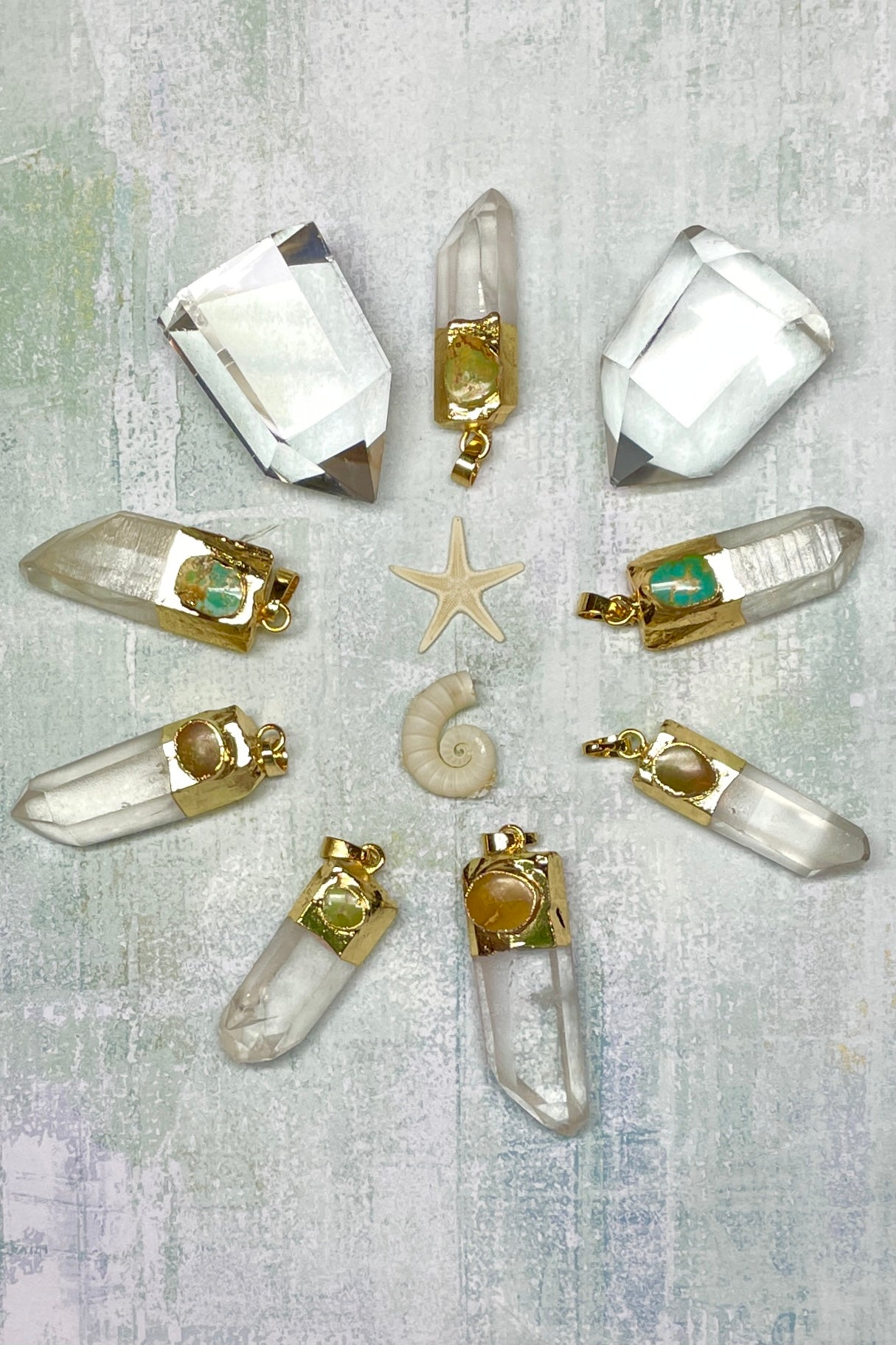 A crystal point that has a hand cut, with turquoise stone at the top, encased in gold tone.