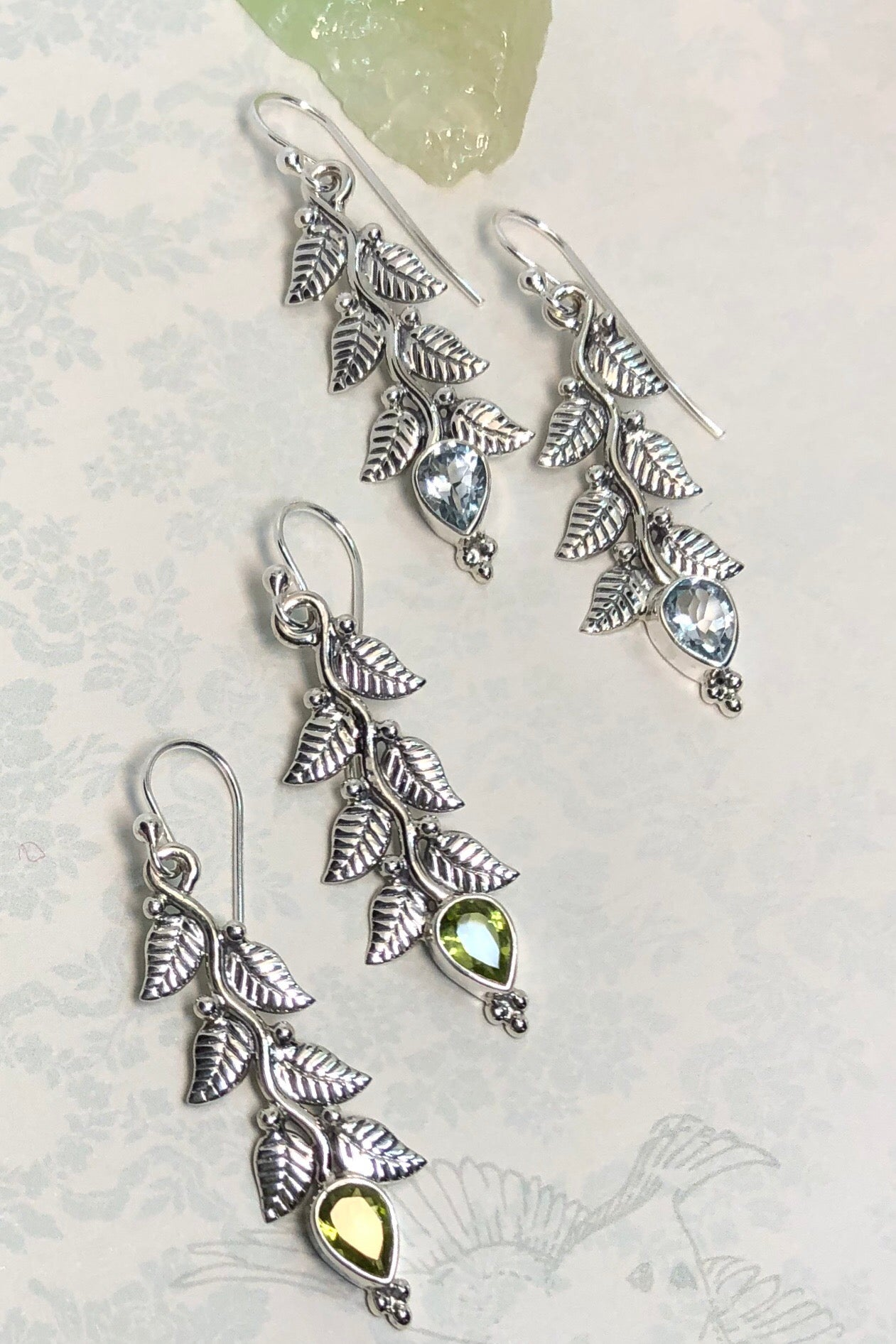 Modern nature design earrings, The Oracle Earrings Vine Gems in Blue Topaz, featuring hanging vine leaves that end with a pretty bright green stone.