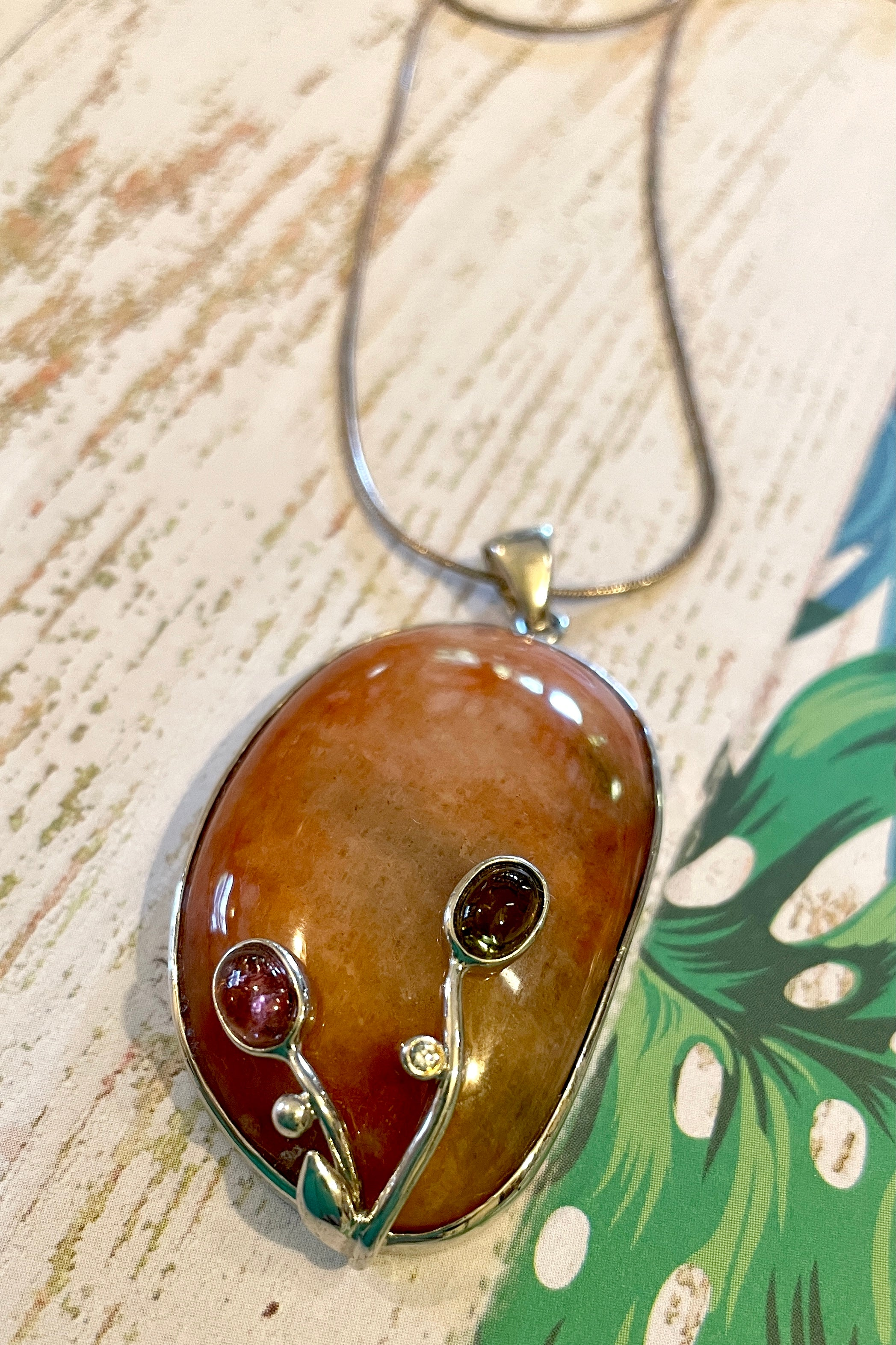 This unusual piece featuring a highly polished rust coloured Quartz shows a depth of coloration that resembles the earth.  Decorated with tiny Tourmaline Cabochons and silver foliage.