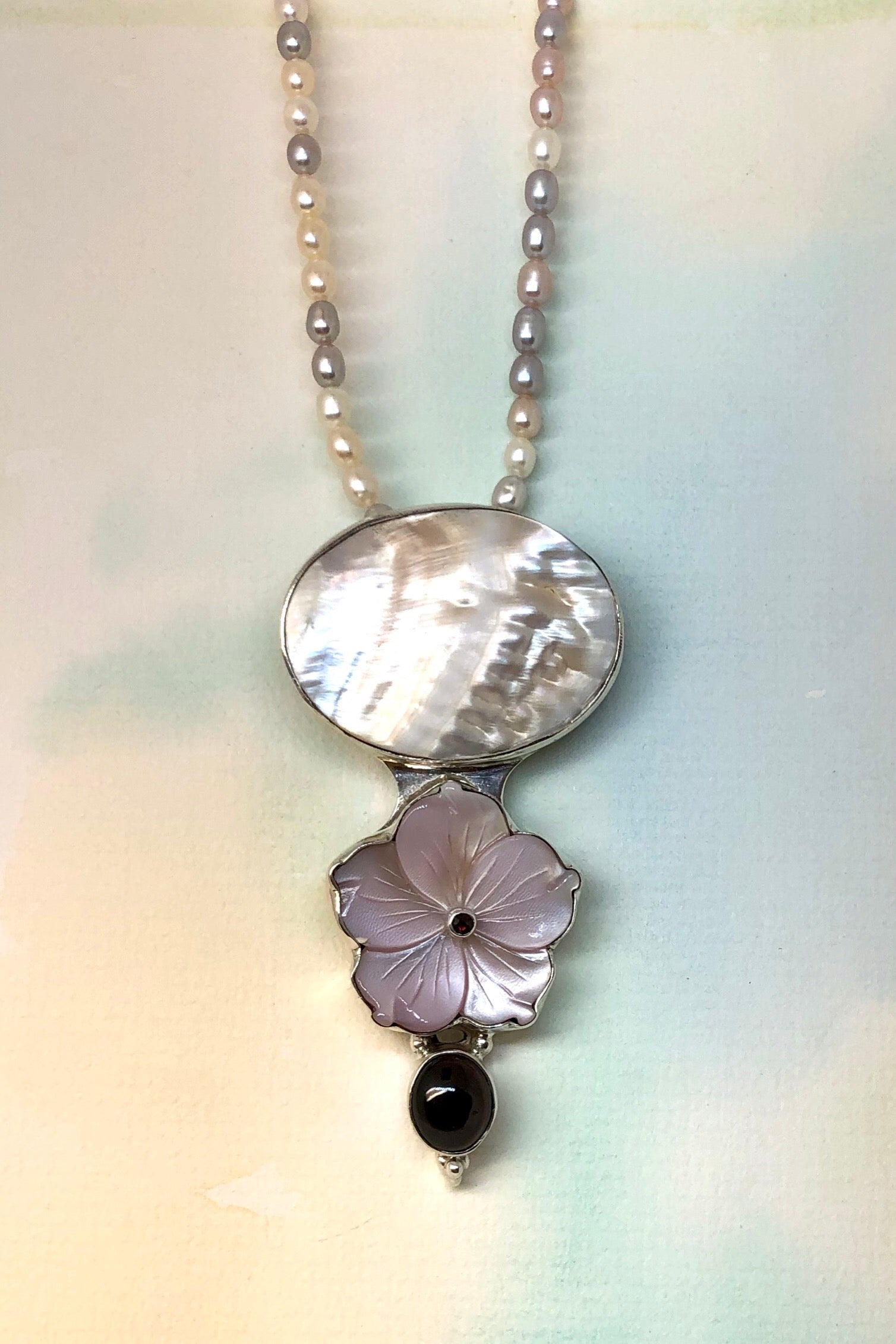 The Echo Pendant The Keeper has a flower carved from beautiful pale pink Mother of Pearl shell and on the top is an oval Mother of Pearl shell in luminescent cream.