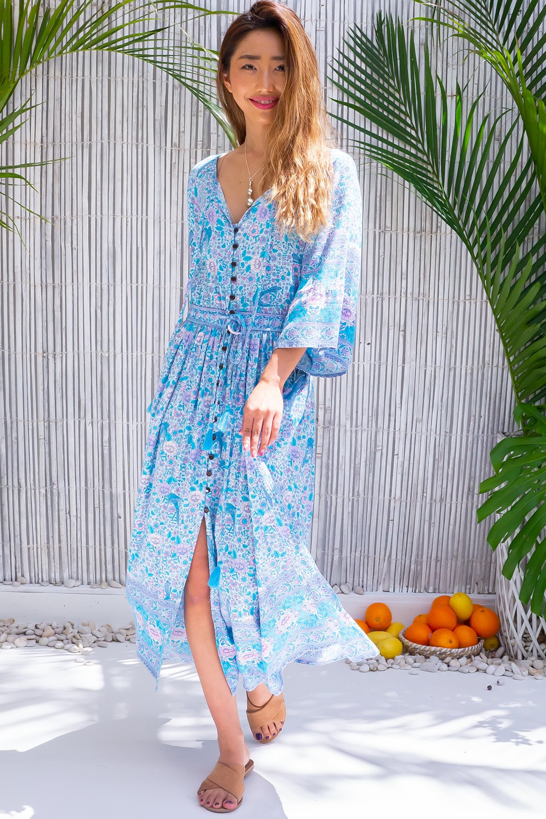 Feel the bohemian vibe in Delilah Skies Dress featuring 3/4 wide sleeves, neck tie detail, functional button front., drawstring waist, soft blue base with folk/bohemian print in blues and lilacs. in woven 100% rayon.