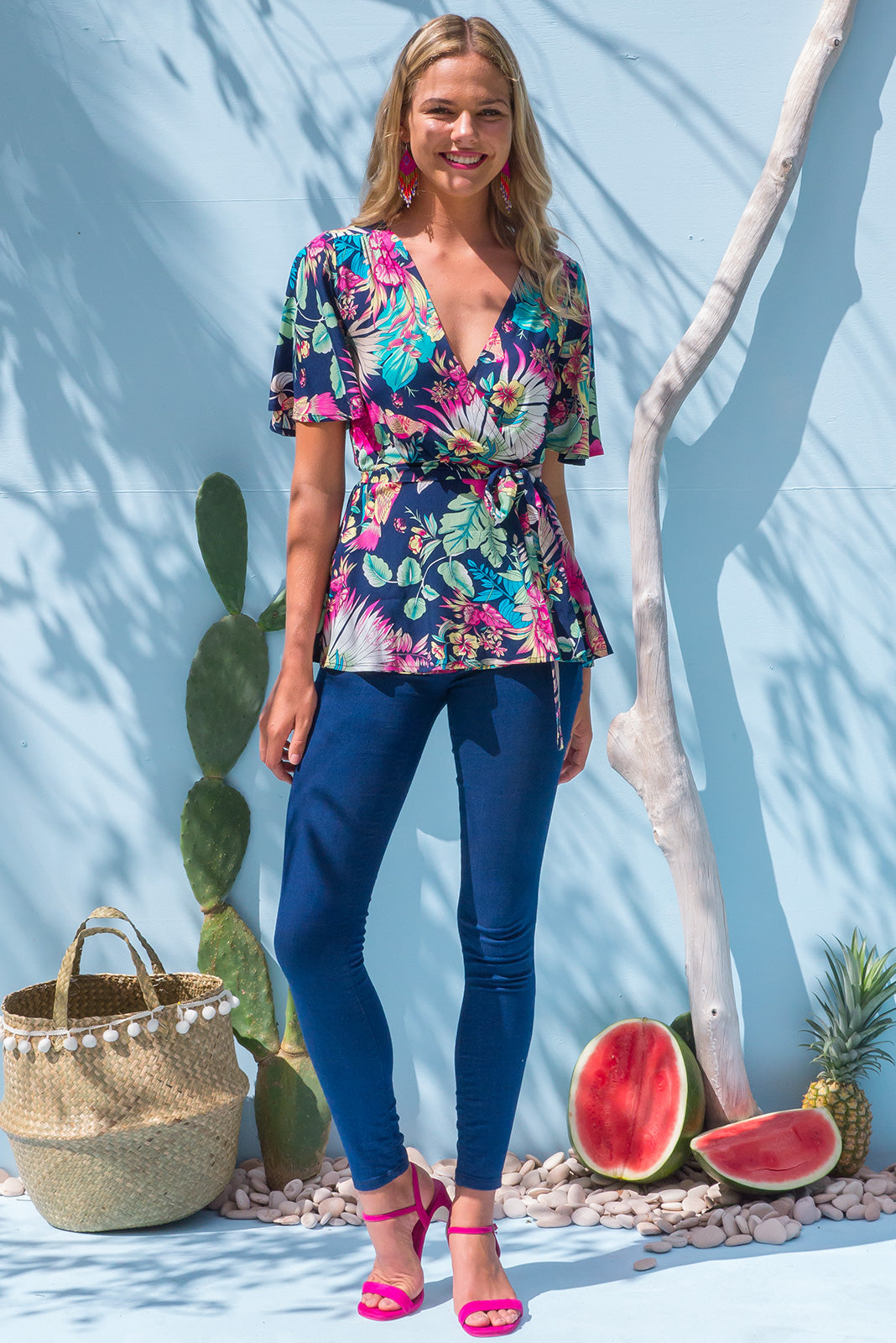 Della Bird of Paradise Wrap Top in a bright navy with a tropical floral and bird print on soft woven rayon the top has petal sleeve and wrap around waist