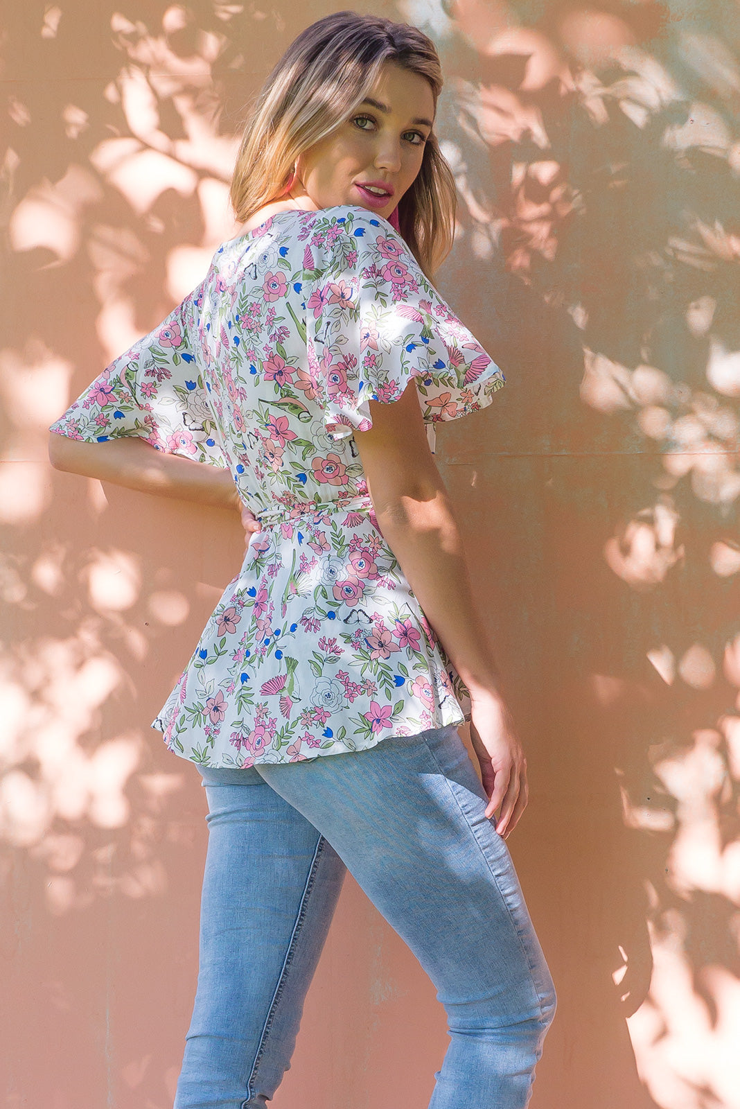 Della Birds & Blooms Wrap Top in a soft floral and bird print on a pale cream the top has petal sleeve and wrap around waist