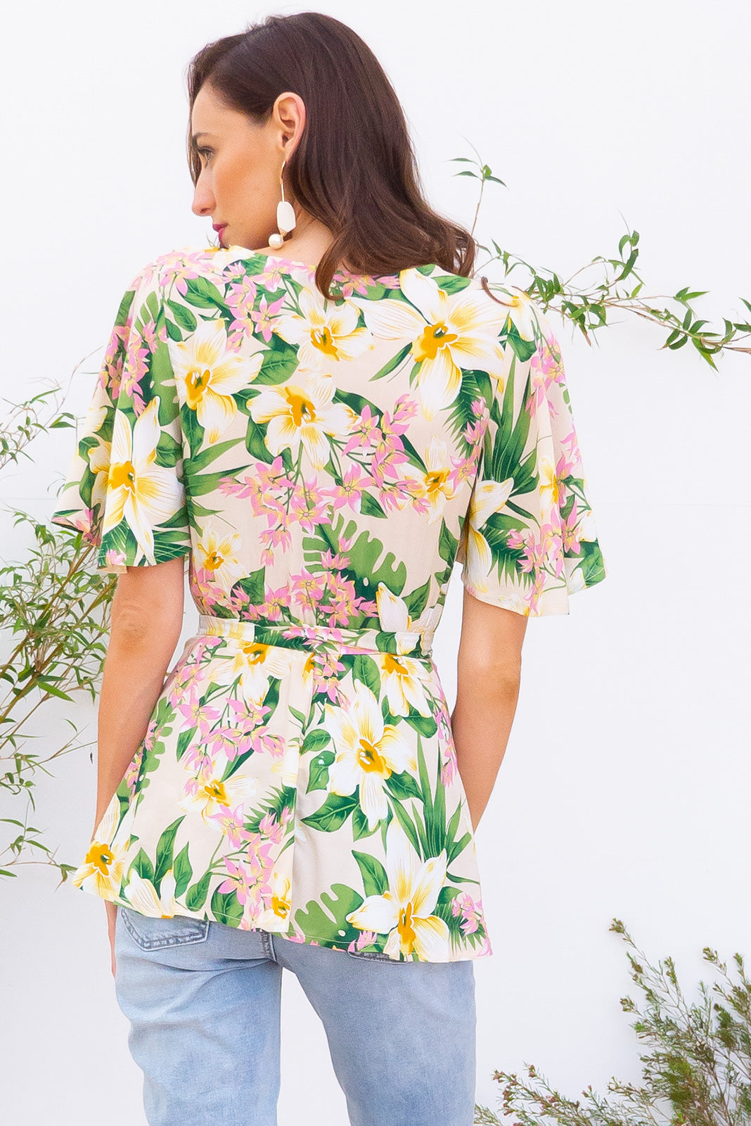 Della Perfect Pastel Wrap Top in a creamy yellow tropical floral  print has petal sleeve and wrap around waist