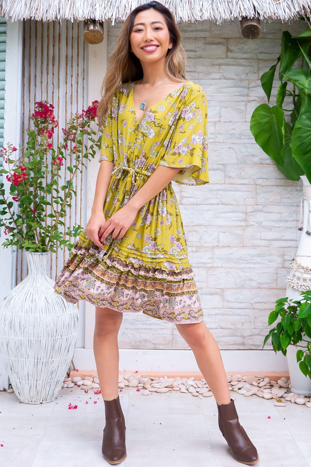 The Dora Olive Mini Dress is a pretty boho frock featuring flutter sleeves, functional button down detailing to drawstring waistline, frill features on skirt with border print, mini length, olive green base with 70's bohemian floral print in pinks, white, green, beige and coffee tones in woven 100% rayon.