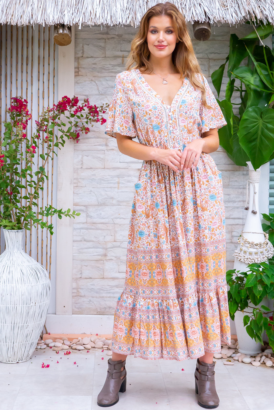 Dorothy Cream Midi Dress is a perfect boho dress featuring flutter sleeves, lace inserts in bust, functional button down detailing to elasticated waistline, frill hem on skirt with border print, midi length, cream base with folk/bohemian print in pinks, blue, beige and amber tones in woven 100% rayon.
