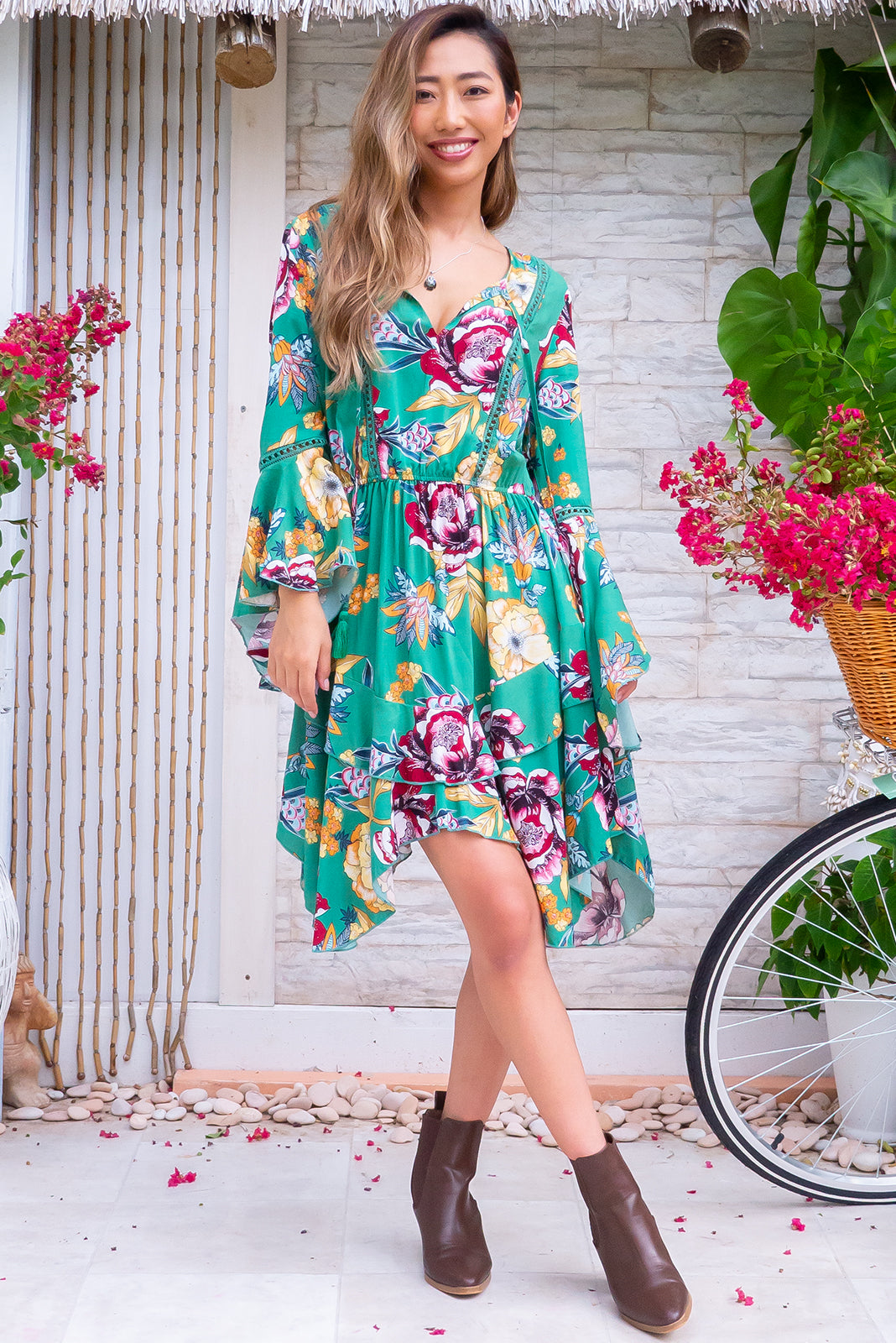 The Dozi Woodstock Green Dress is a super retro frock featuring tie up keyhole neckline, lace inserts in bust and sleeves, handkerchief hem bell sleeves, elasticated waist, handkerchief hem skirt, jade green base with graphic, colourful floral print in woven 100% rayon.