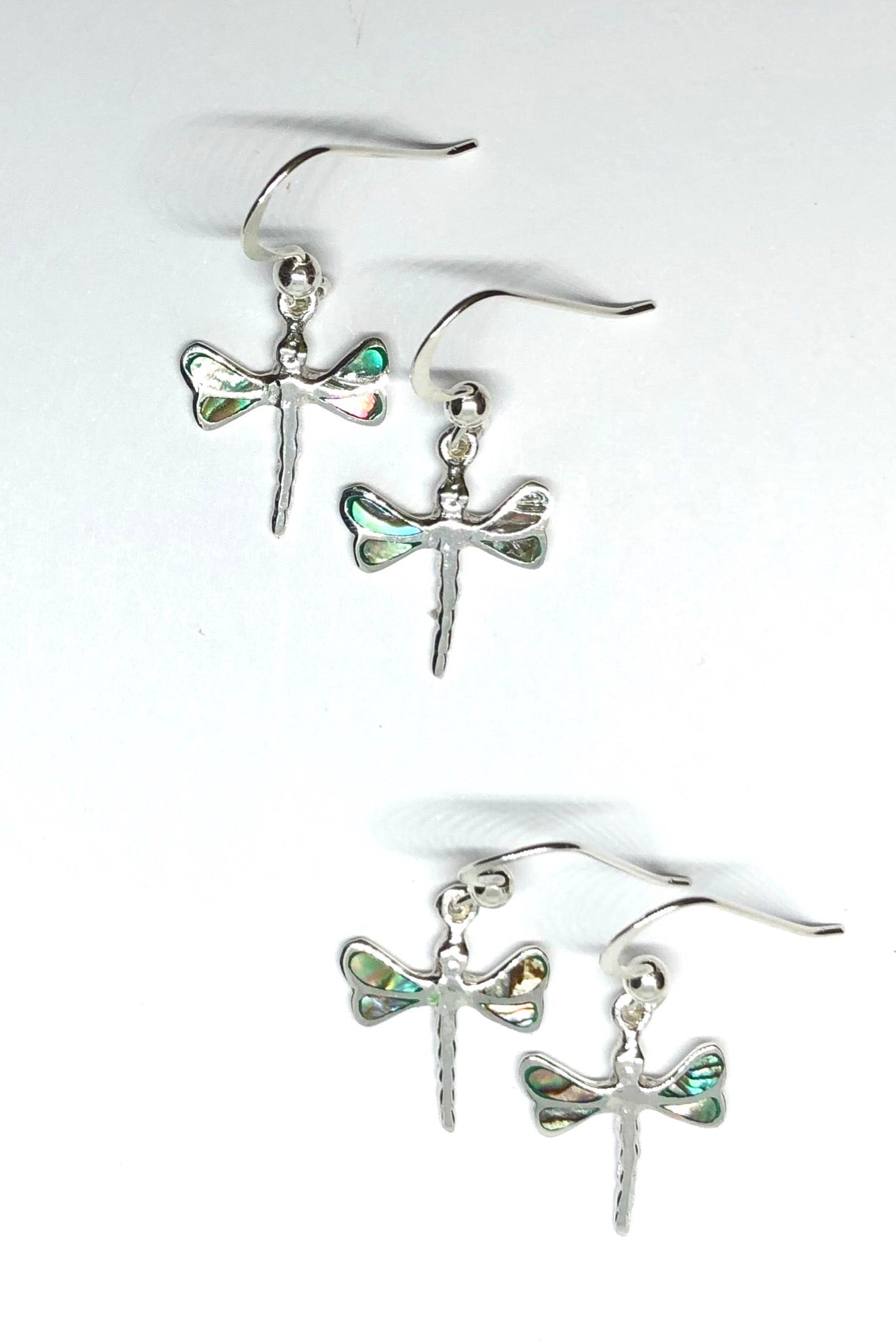 A tiny and delicate 925 silver pair of earrings featuring mysterious Paua shell on thewings