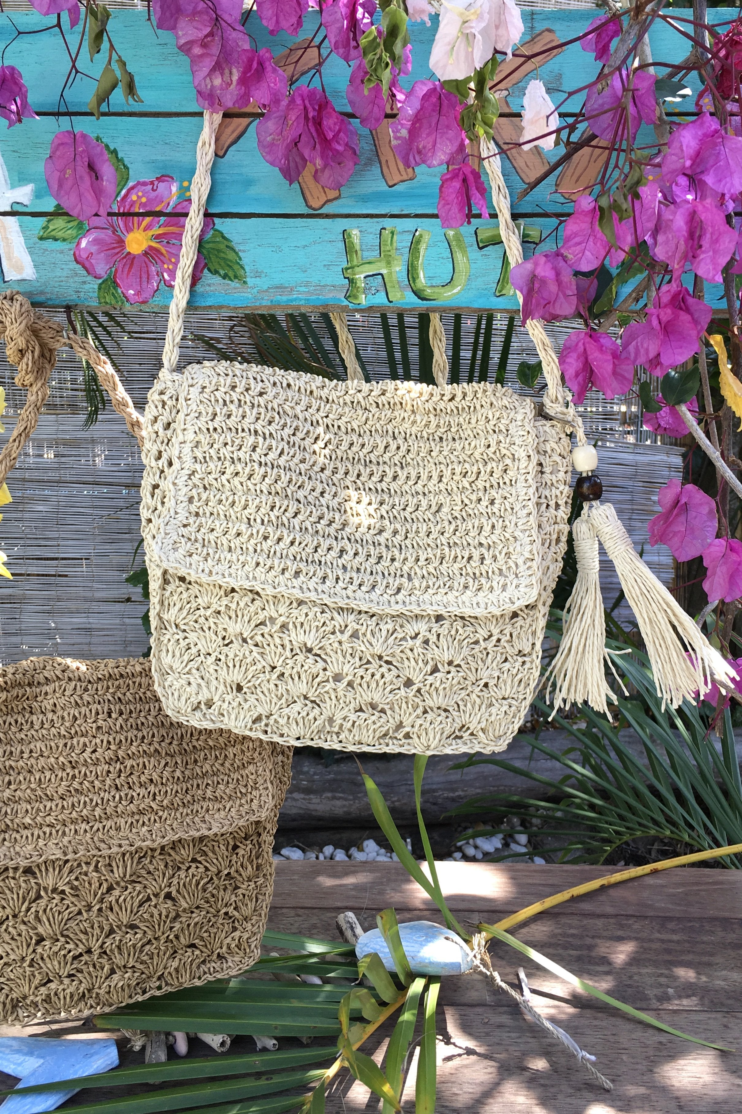 The Bag Lillie Loves Shelley Cream or Tan is an alternative woven straw bag with a cool tassel and bead feature, and a front cover flag and zip